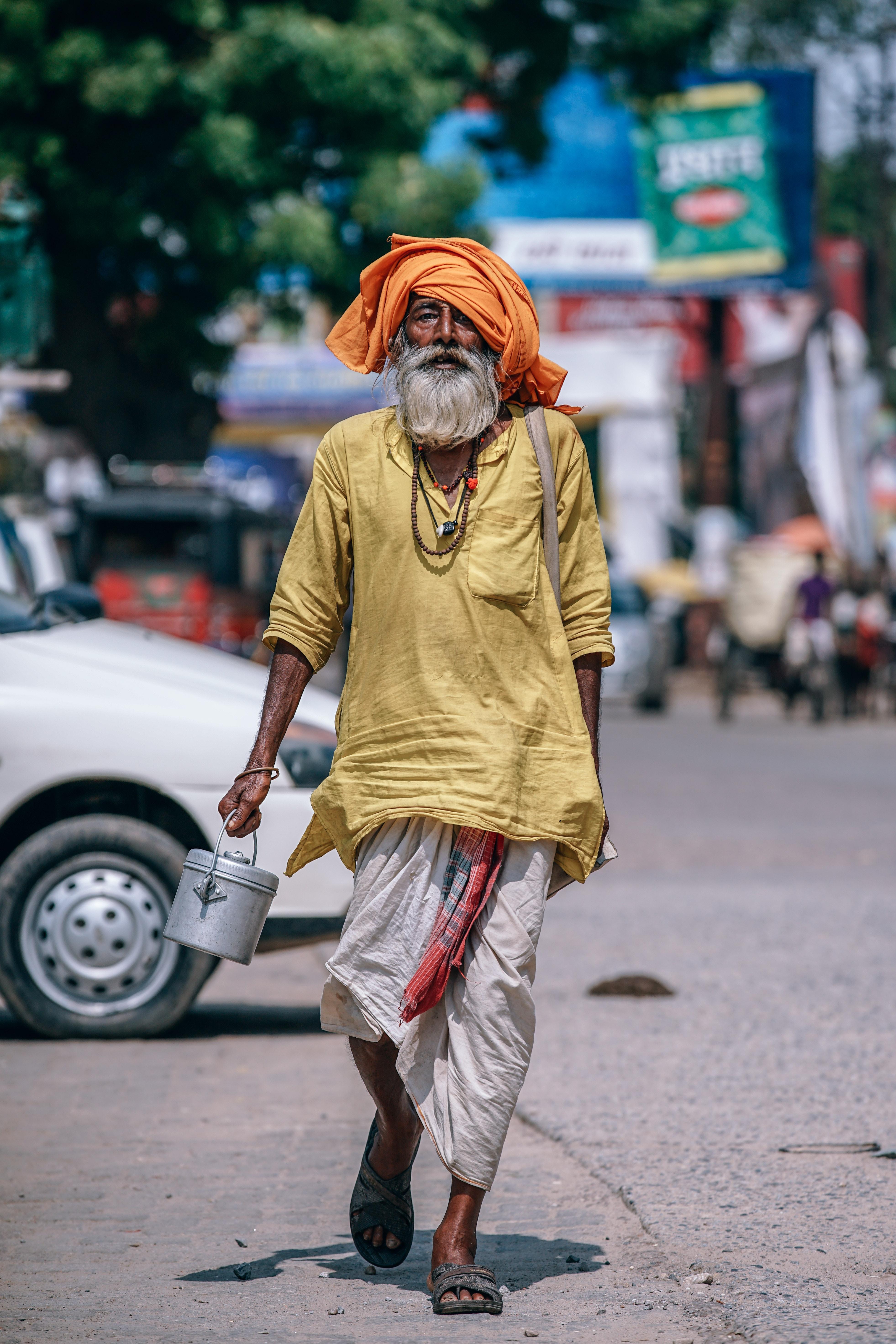 Man walking on street carrying metal bucket photo