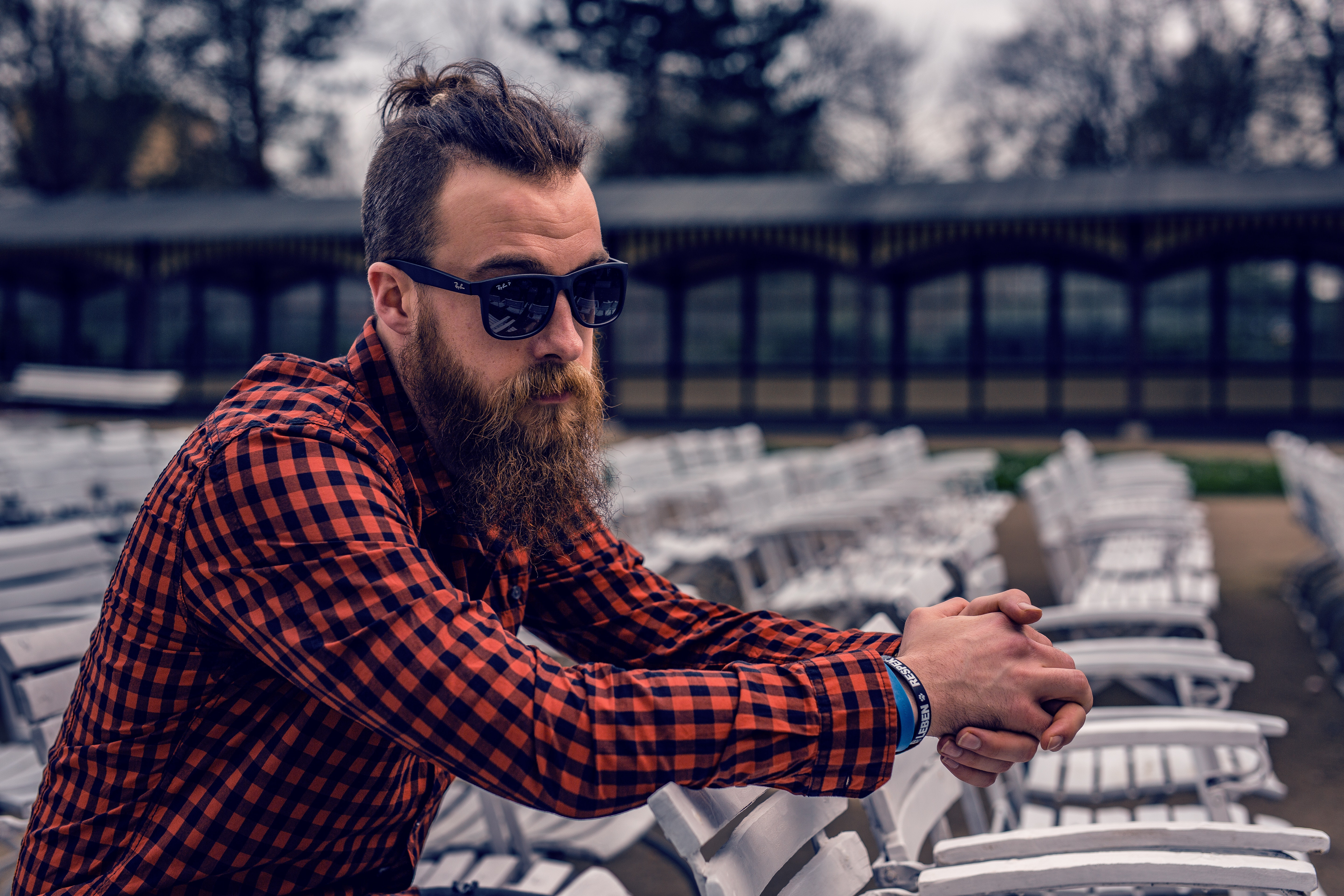 Man wearing black and red checkered long sleeve shirt wearing black wayfarer sunglasses sitting on white wooden chair photo