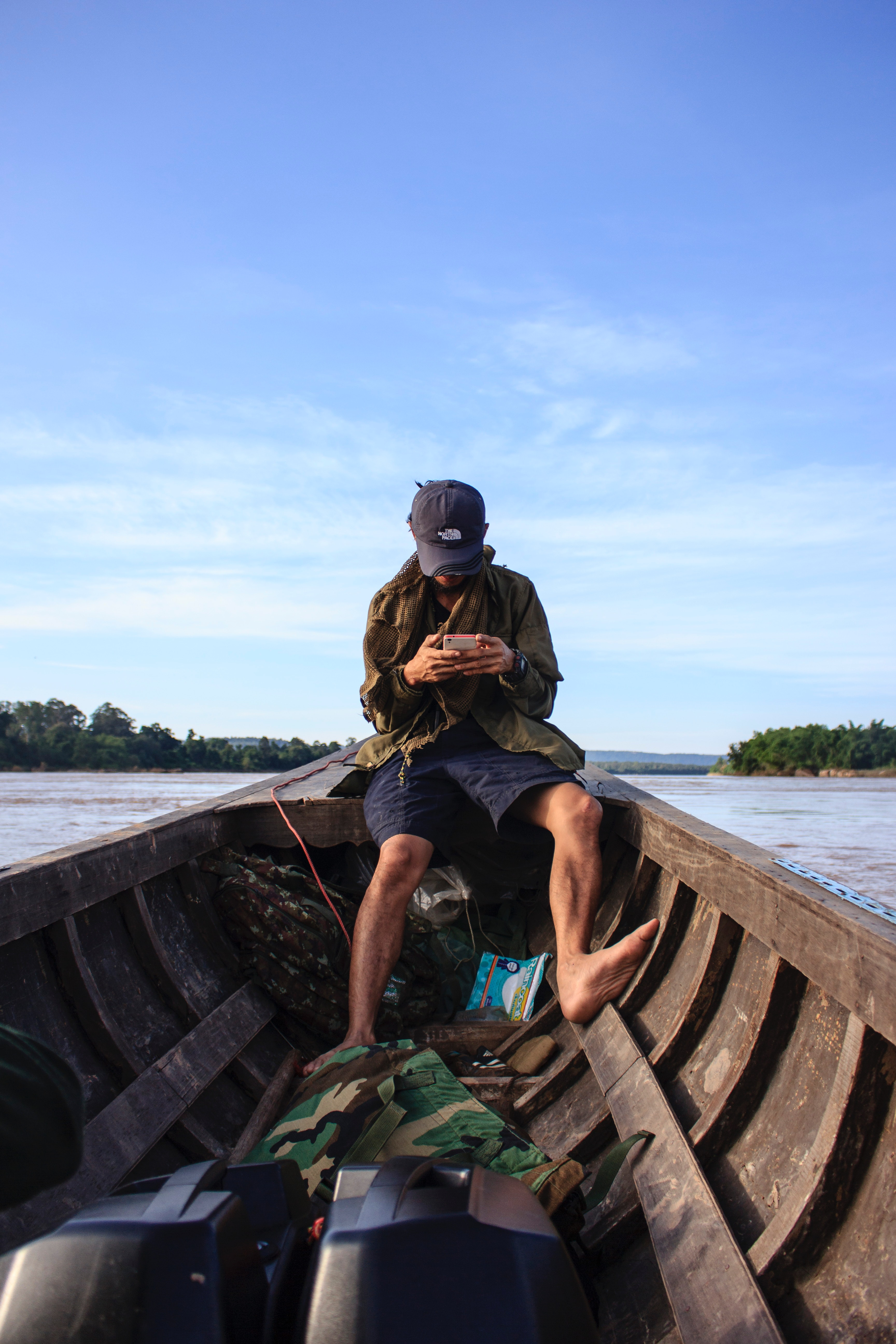 Man Wearing Black Cap Sitting Inside a Boat, Background, Watercraft, Water, Trees, HQ Photo