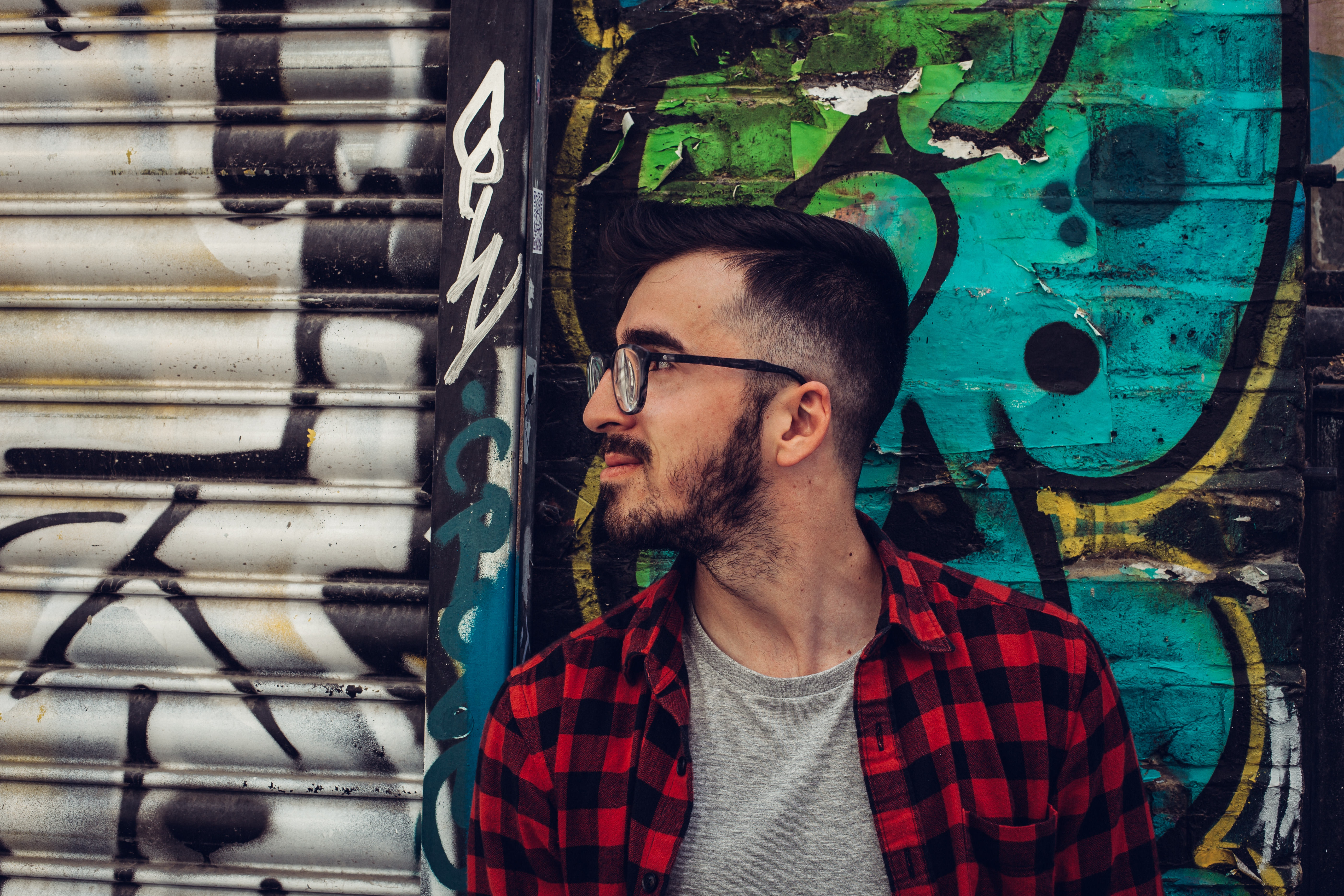 Man Wearing Black Framed Eyeglasses Standing Beside Blue and Black Wall, Abandoned, Person, Wall, Vandalism, HQ Photo