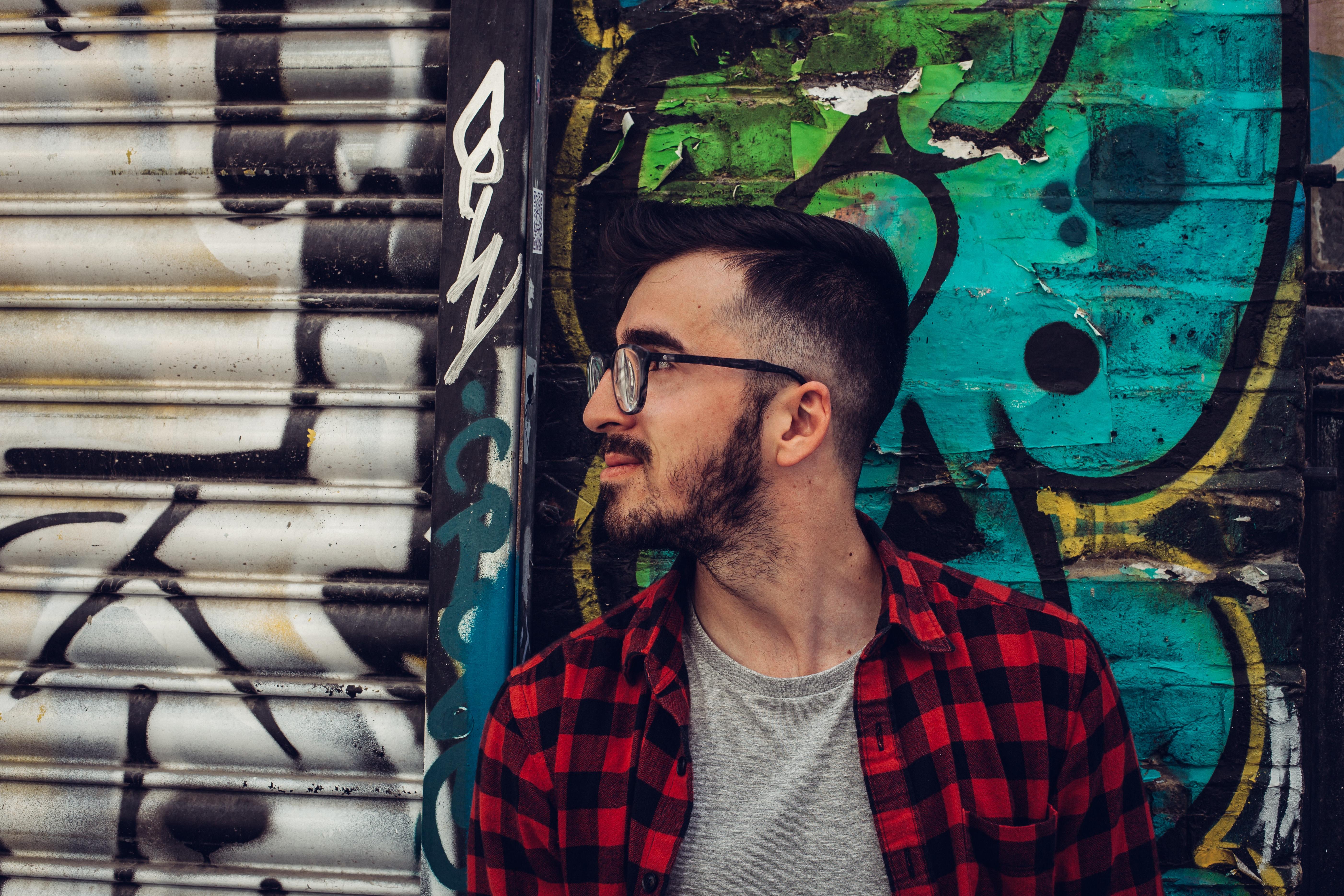 Man wearing black framed eyeglasses standing beside blue and black wall photo