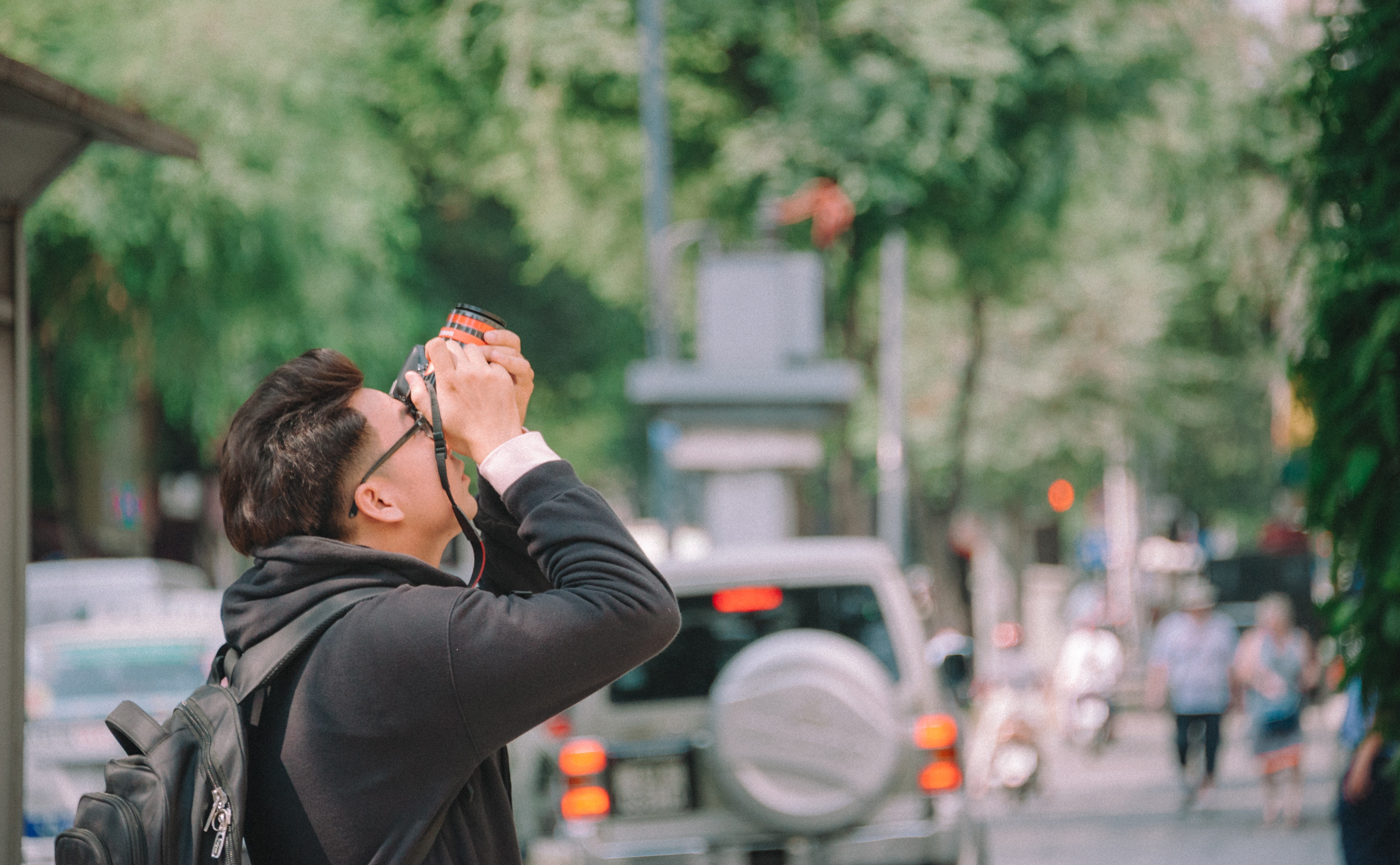 Man Wearing Black Hoodie Holding Dslr Camera Shooting on Upper Direction, Pavement, Young, Wear, Walking, HQ Photo