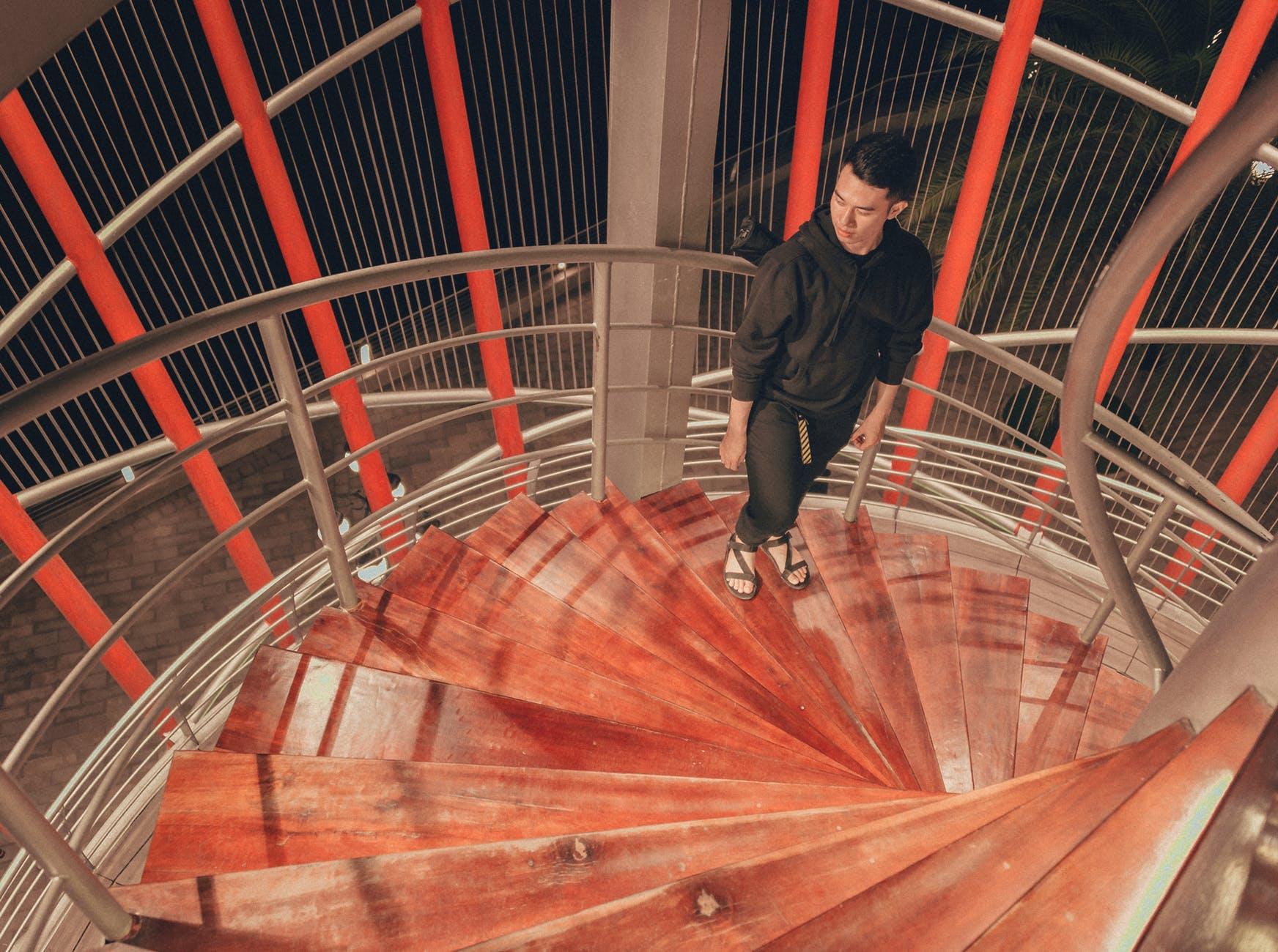 Man wearing black hoodie standing on staircase photo