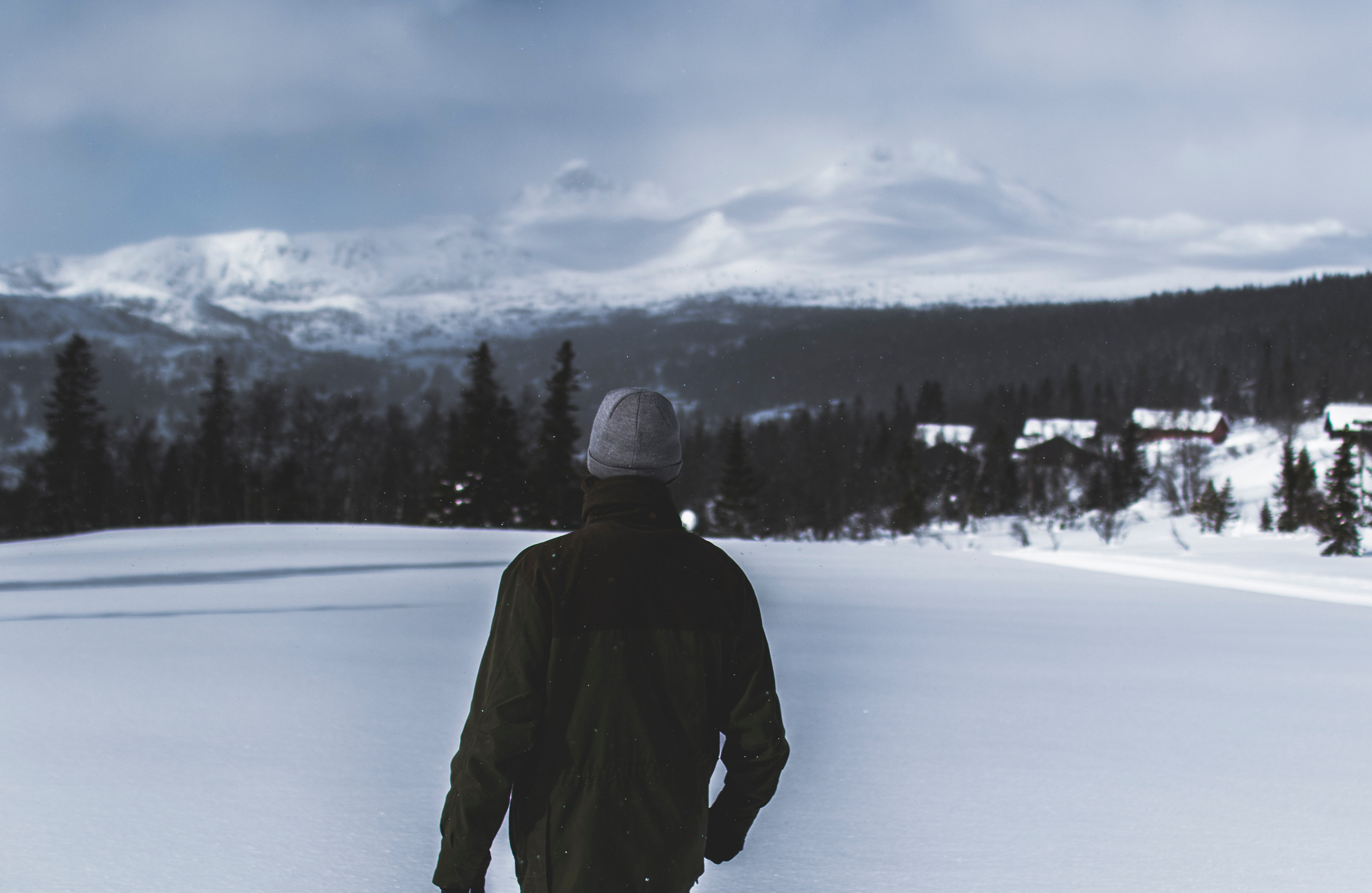 Man wearing black jacket walking in the snow photo
