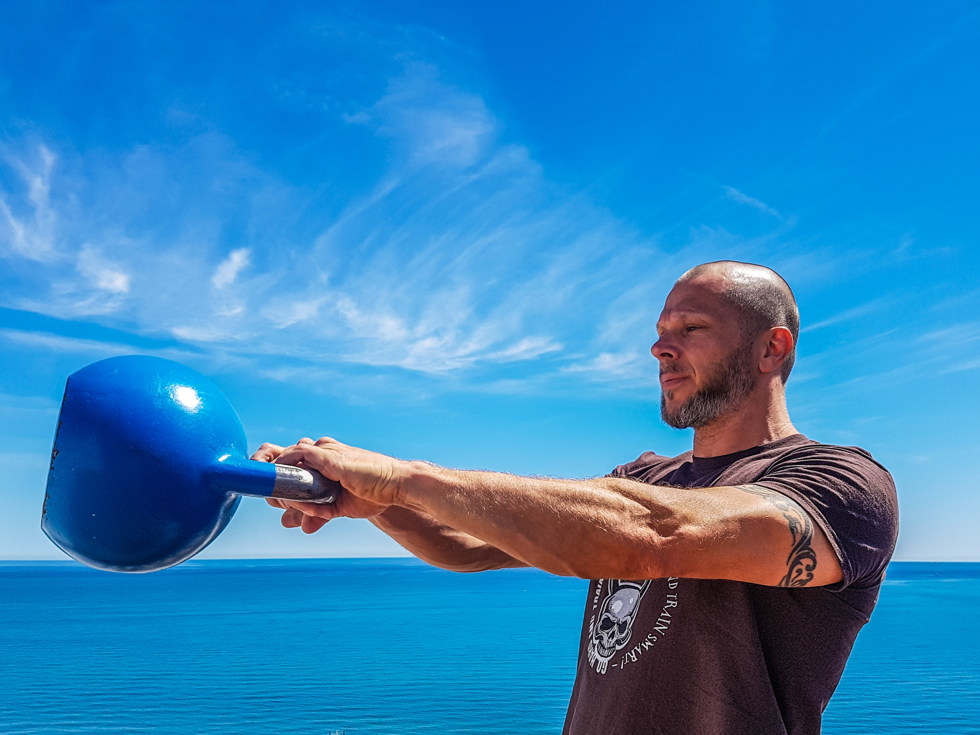 Man Wearing Black Shirt Holding Kettle Bell Near Body of Water, Adult, Ocean, Tattoo, Strong, HQ Photo