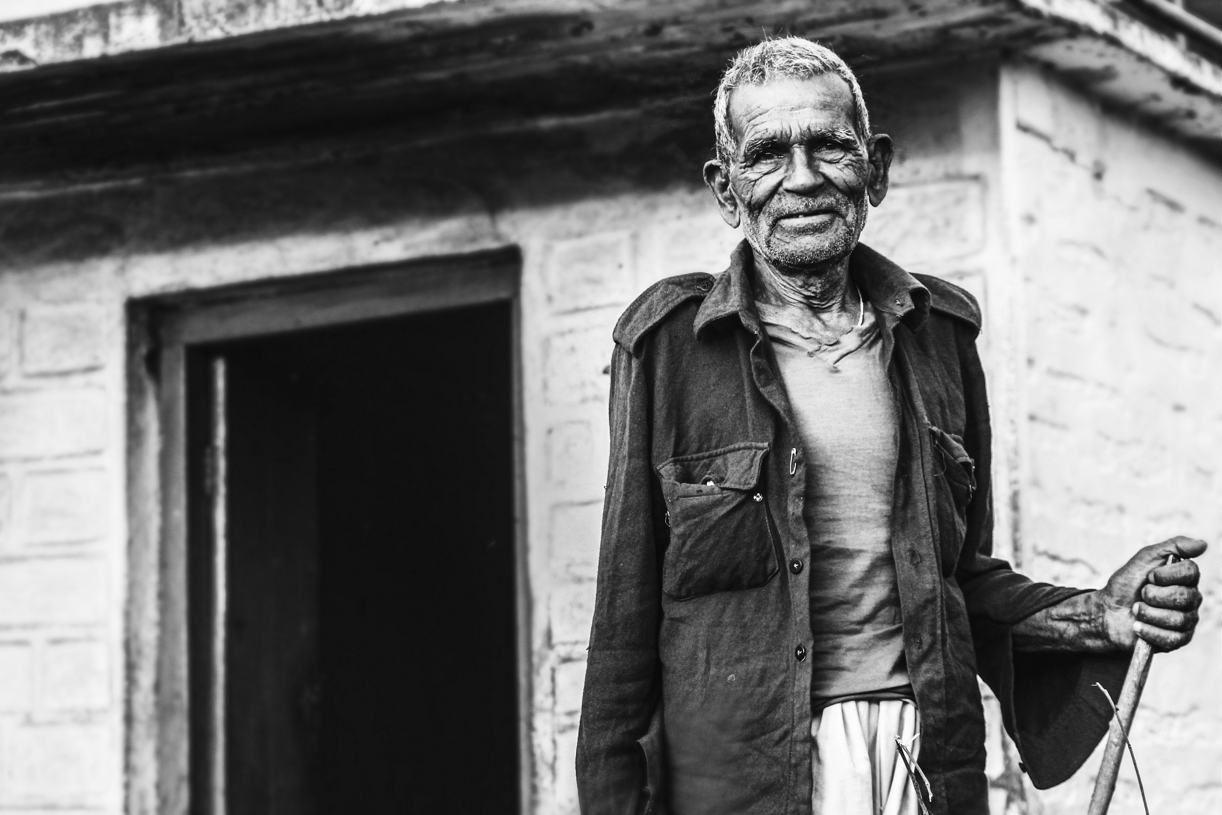 Man Wearing Button-up Shirt Standing Near Concrete House Greyscale Photo, Adult, Old, Wear, Village, HQ Photo