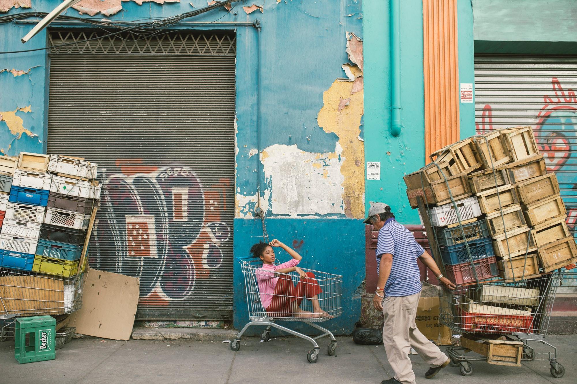 Man wearing gray cap and blue shirt holding shopping cart photo