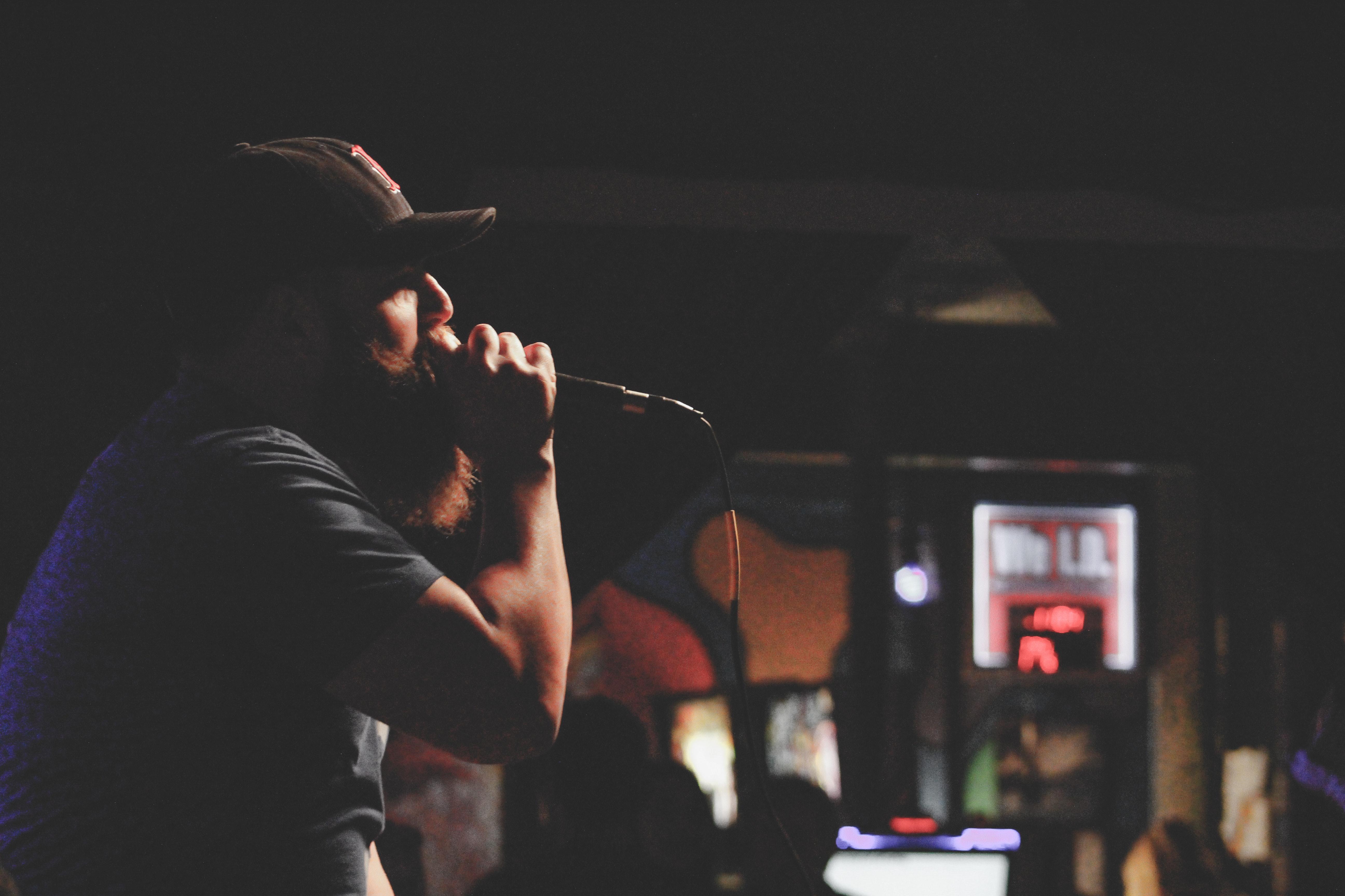 Man wearing grey shirt and black cap singing using corded microphone photo