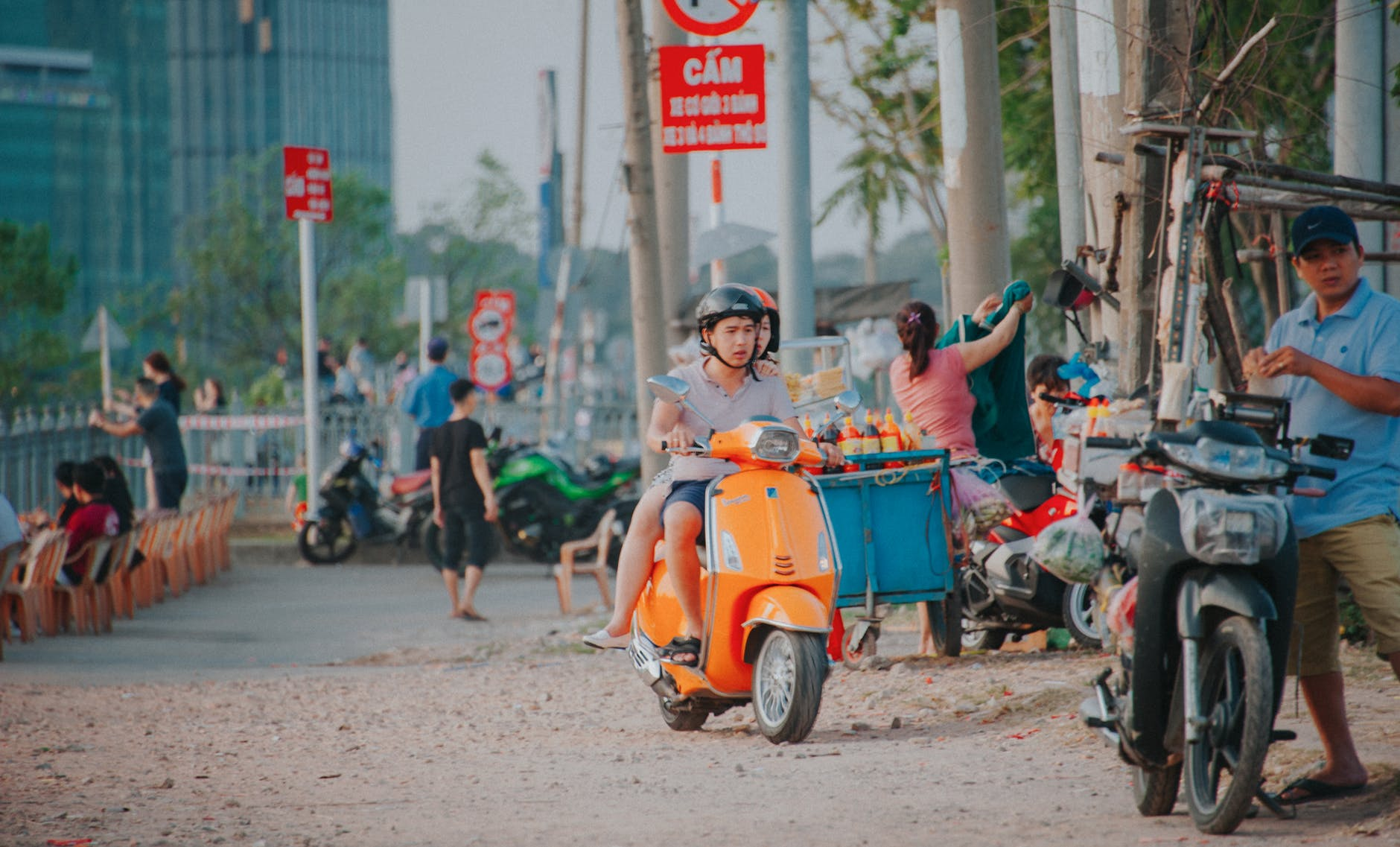 Man wearing grey shirt riding on orange motor scooter at daytime photo
