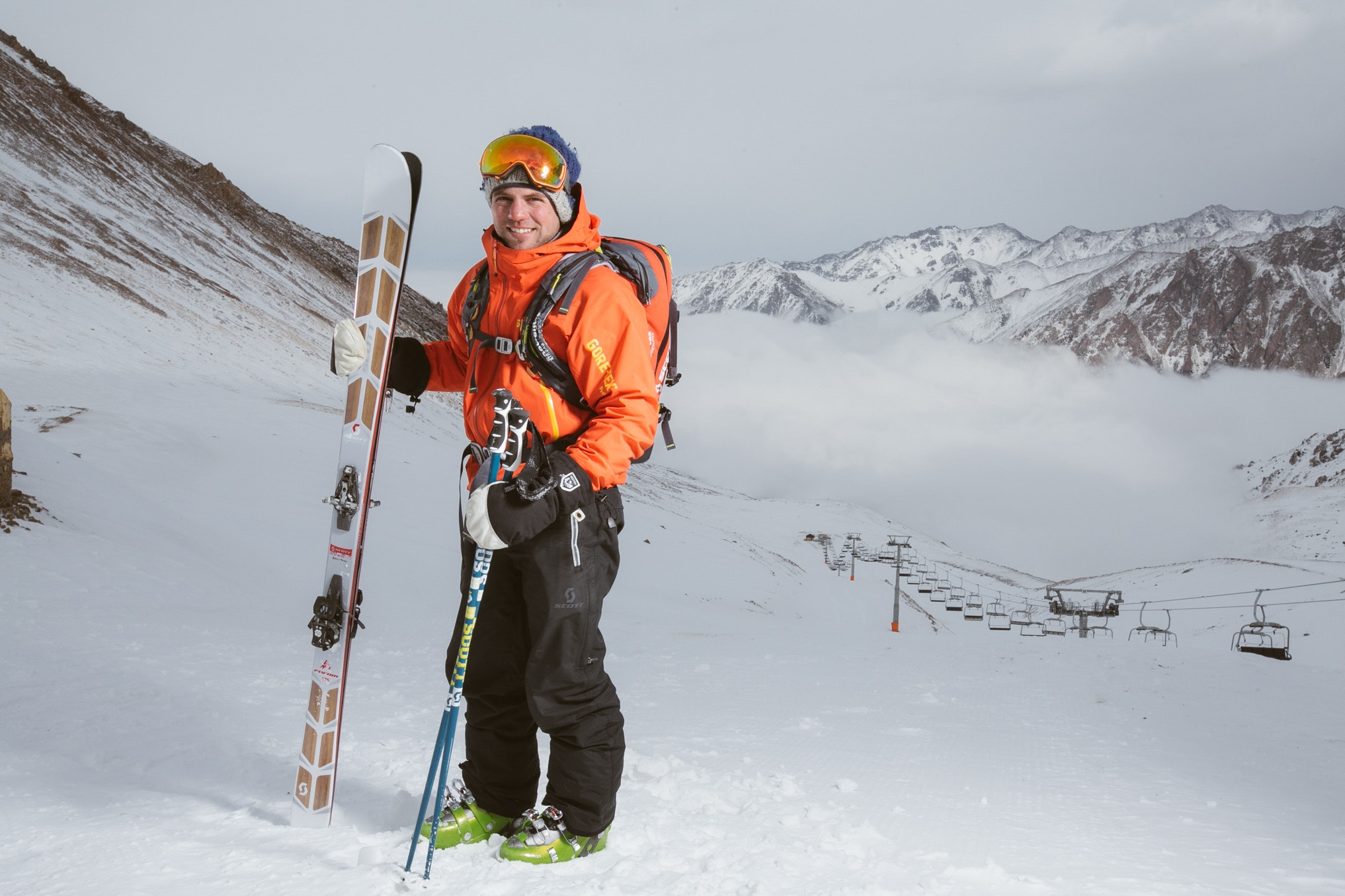Man wearing orange and black snowsuit with ski set on snow near cable cars photo