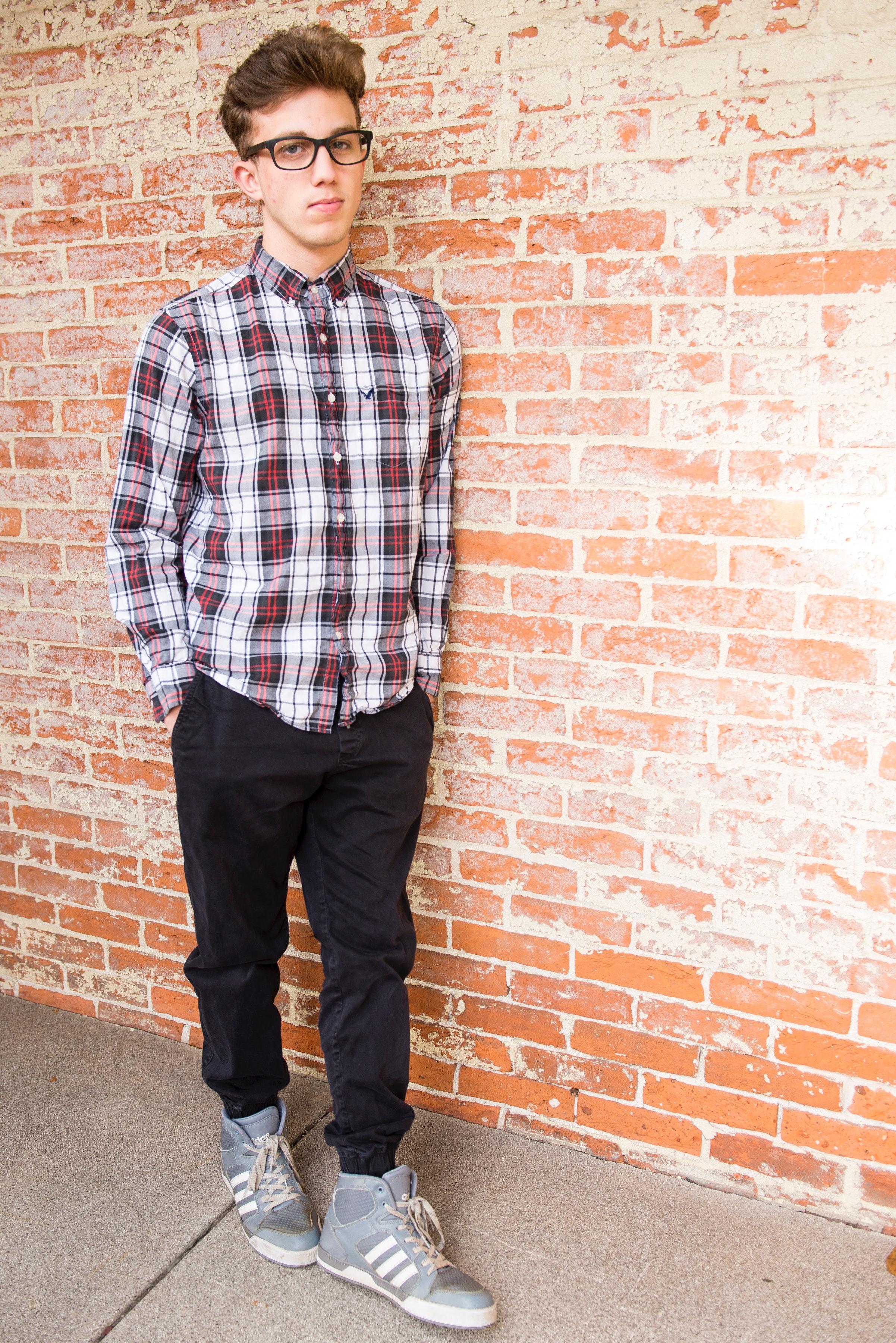 Man wearing plaid dress shirt and black pants photo
