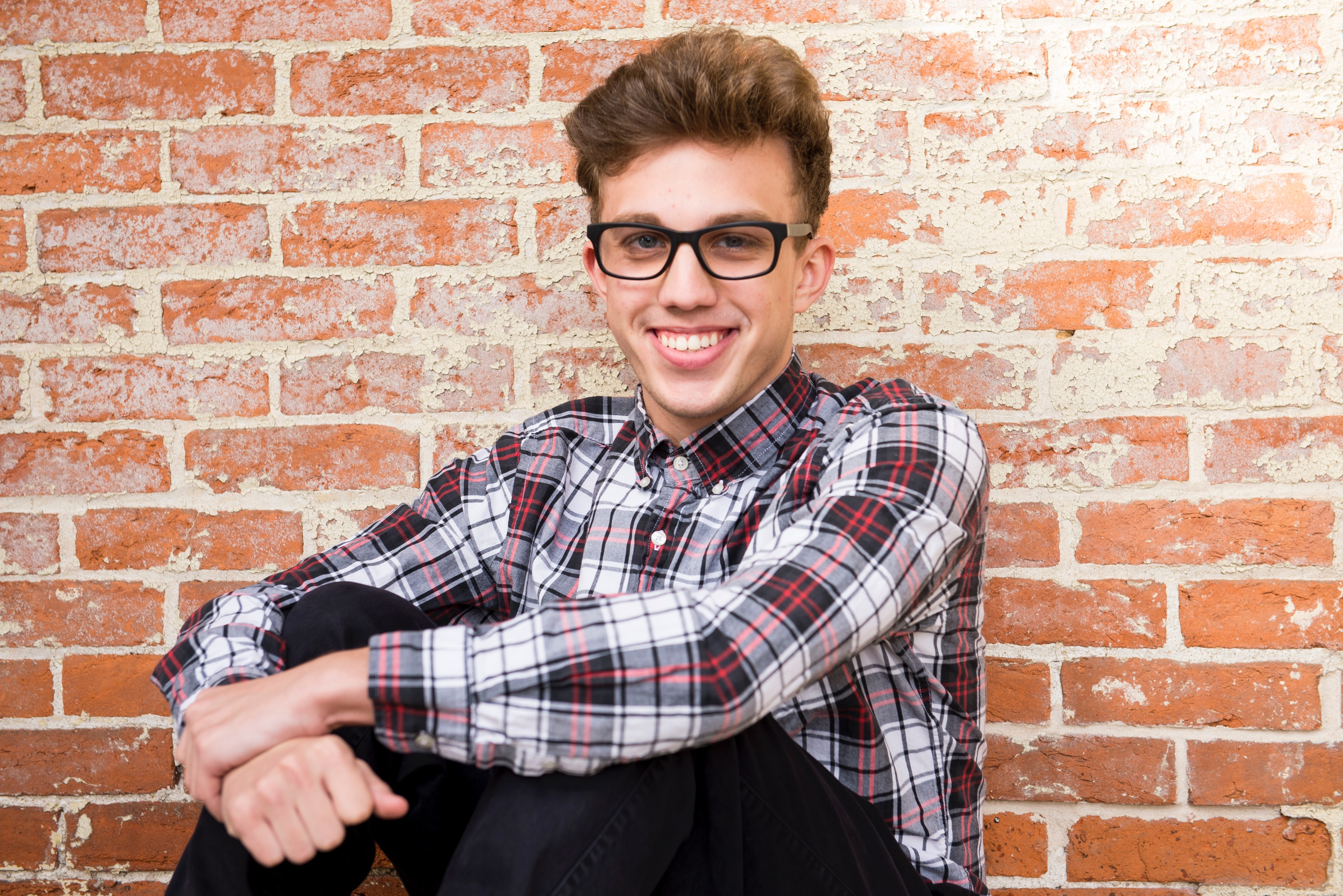 Man Wearing Plaid Dress Shirt And Black Pants Sitting Near Brown Brick Wall, Boy, Portrait, Young, Wear, HQ Photo