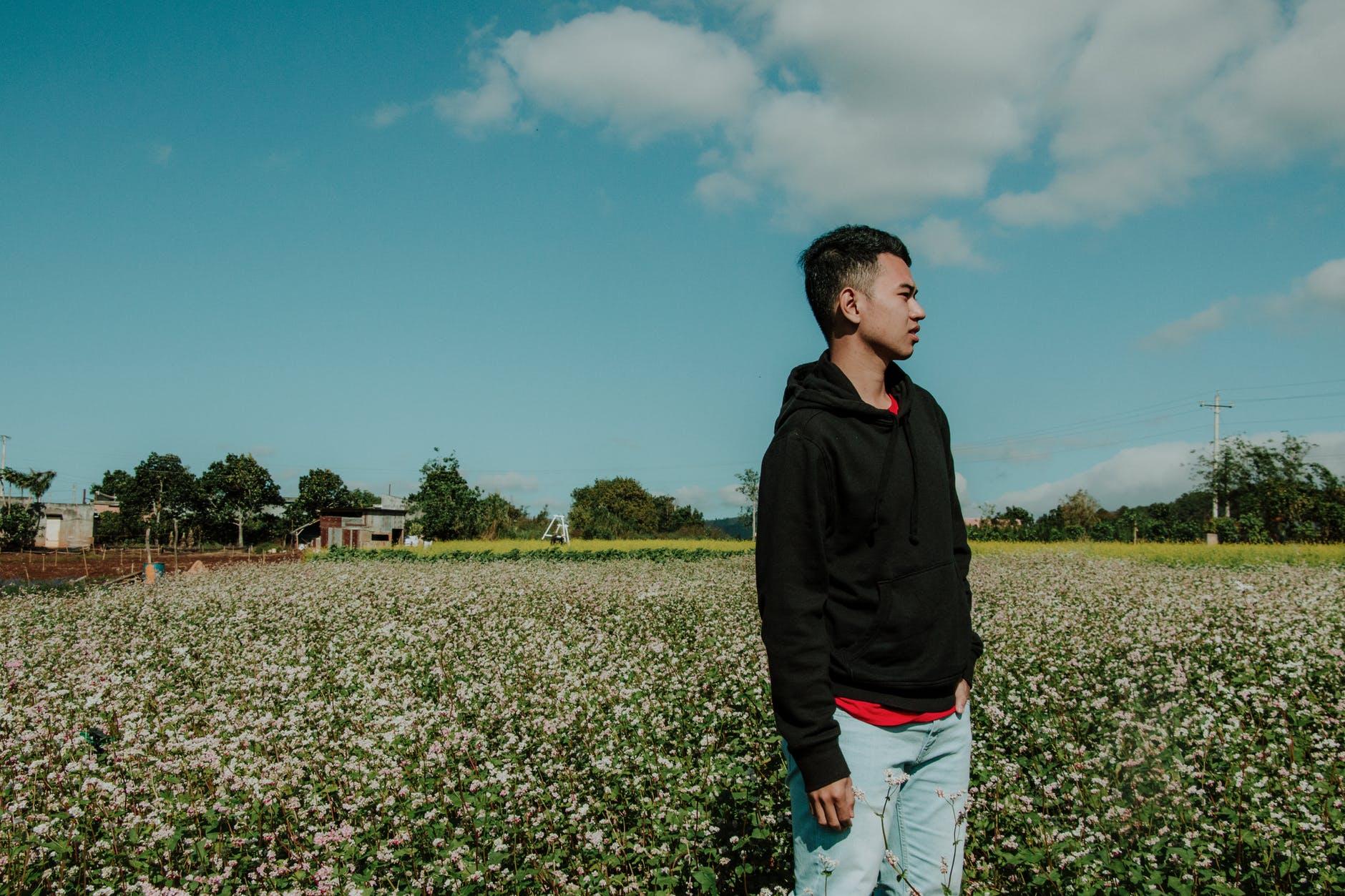 Man wearing pullover hoodie standing on flower field photo