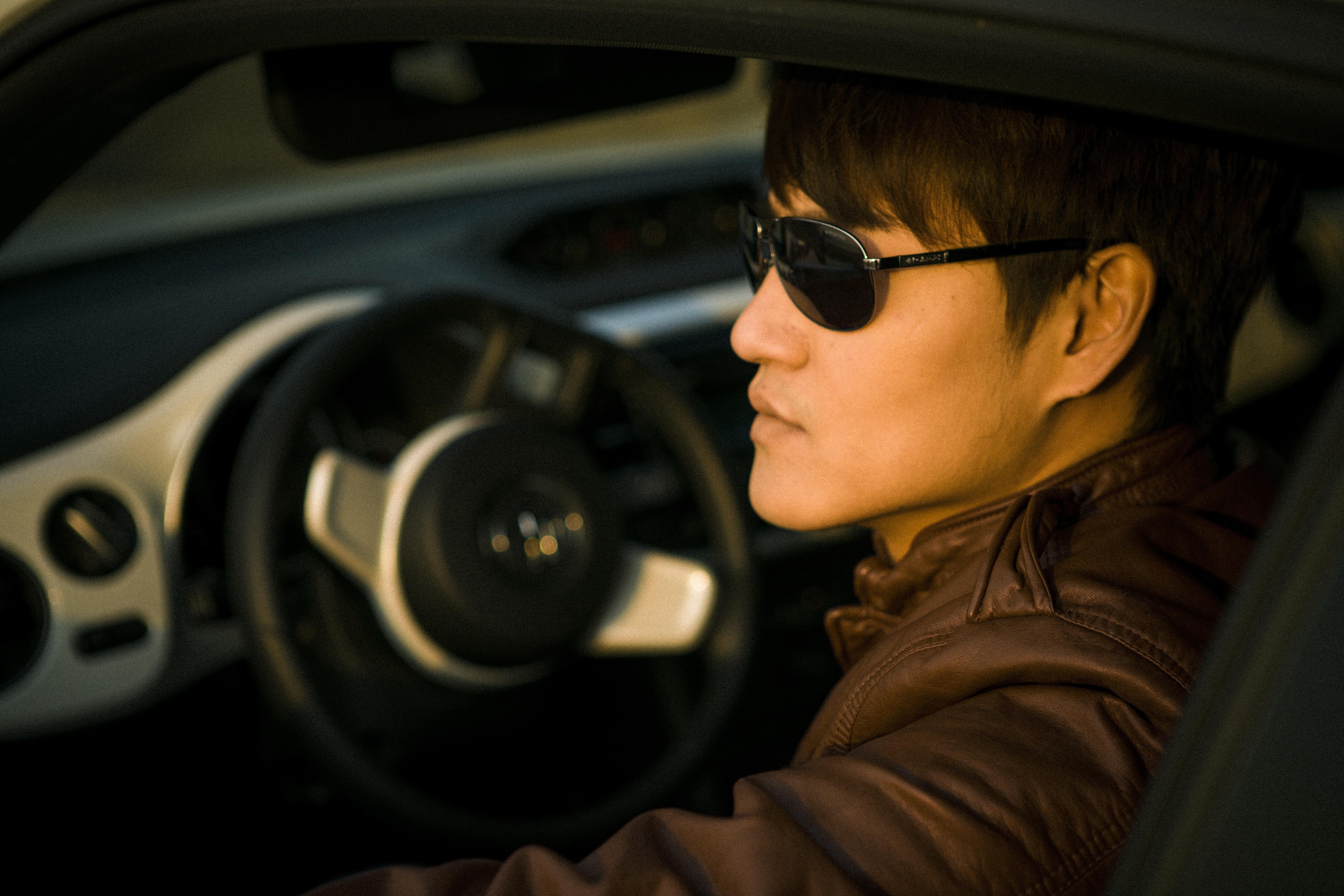 Man wearing sunglasses sitting on driver's seat photo