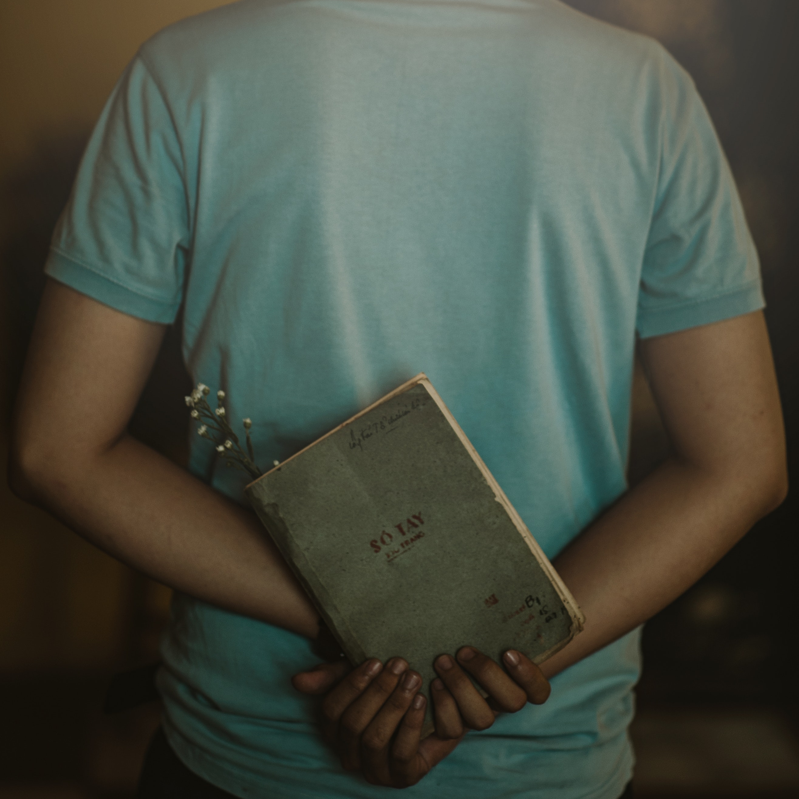 Man wearing t-shirt holding book photo