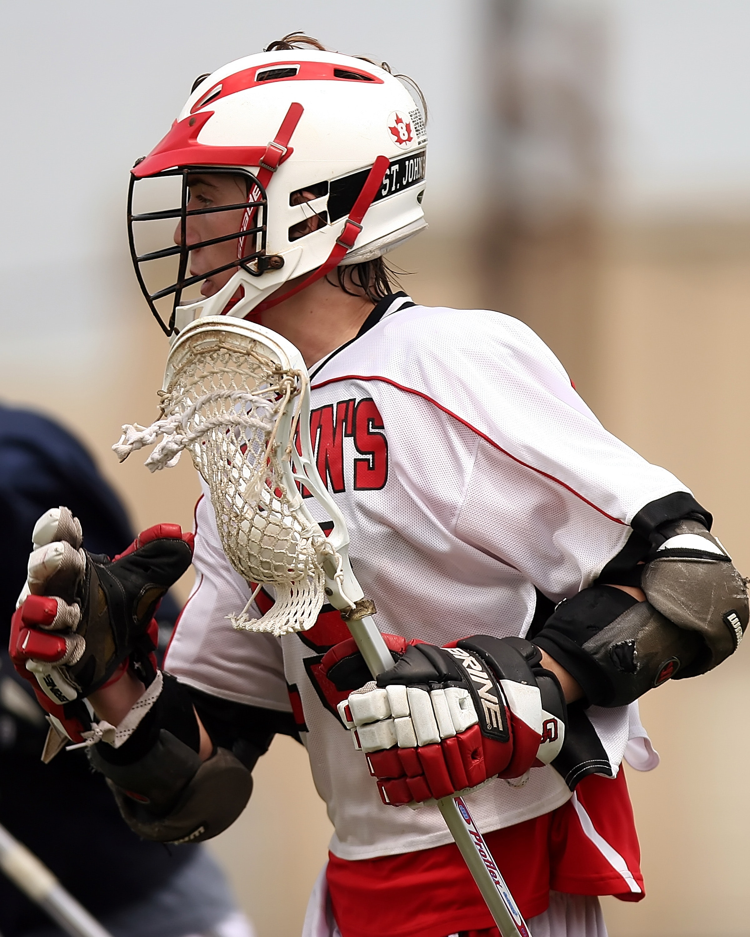 Man wearing white and red lacrosse uniform photo