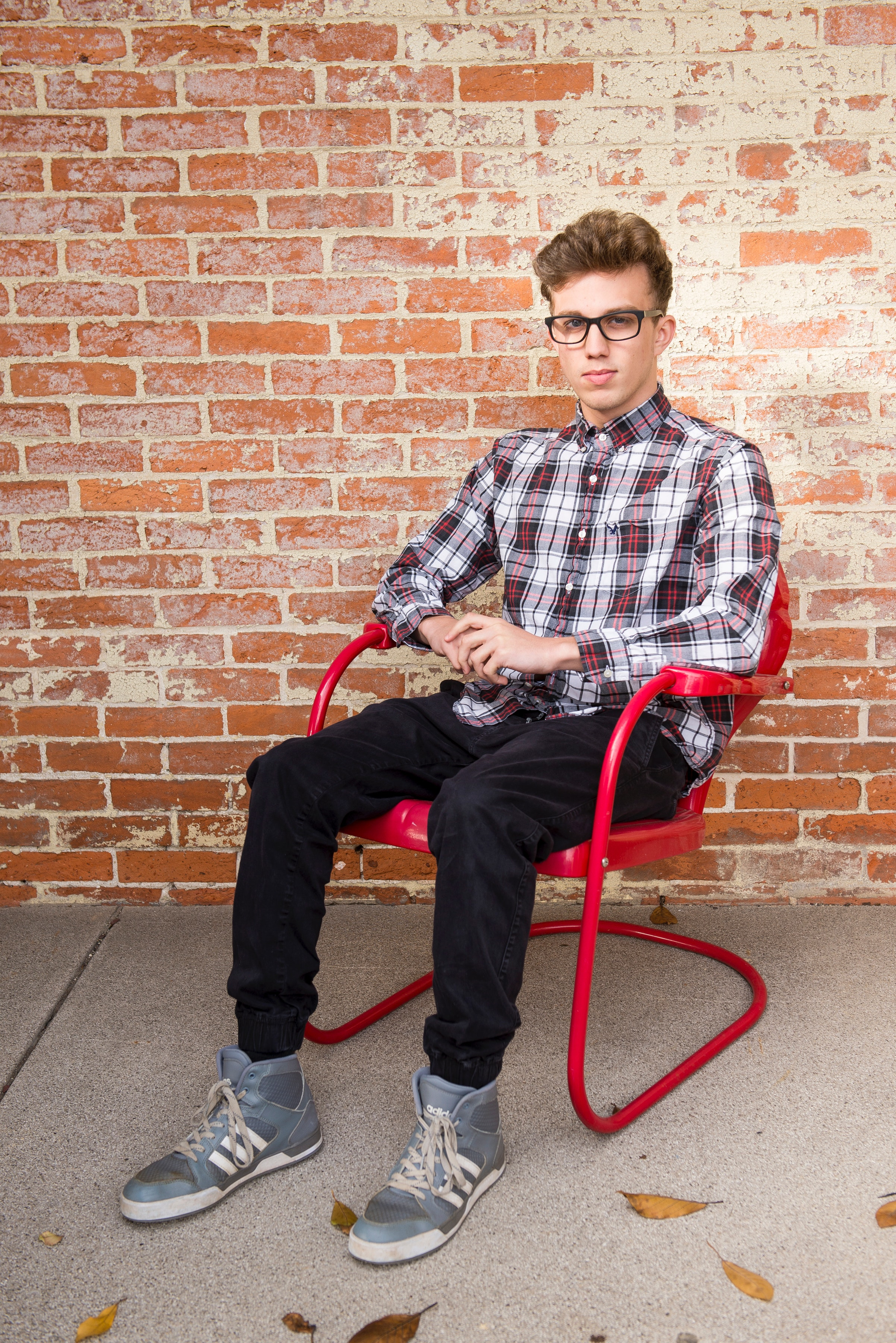 Man Wearing White And Red Long Sleeve Shirt Sitting On Red Steel Armchair, Adolescent, Boy, Brick wall, Casual, HQ Photo