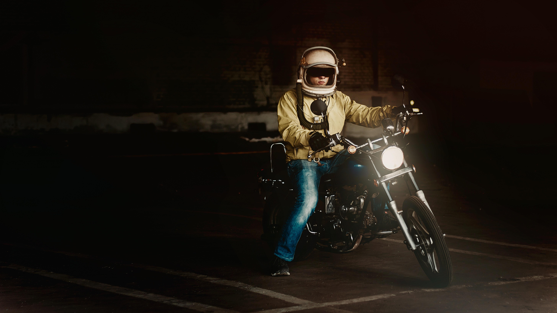 Man wearing white full face helmet riding on standard motorcycle photo