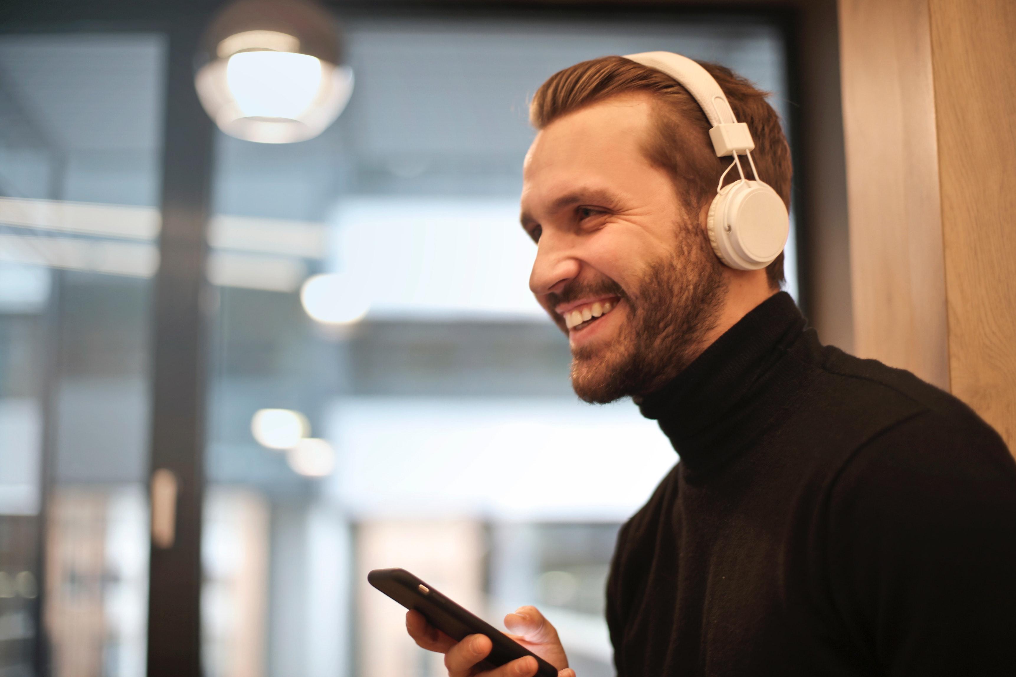 Man wearing white headphones listening to music photo