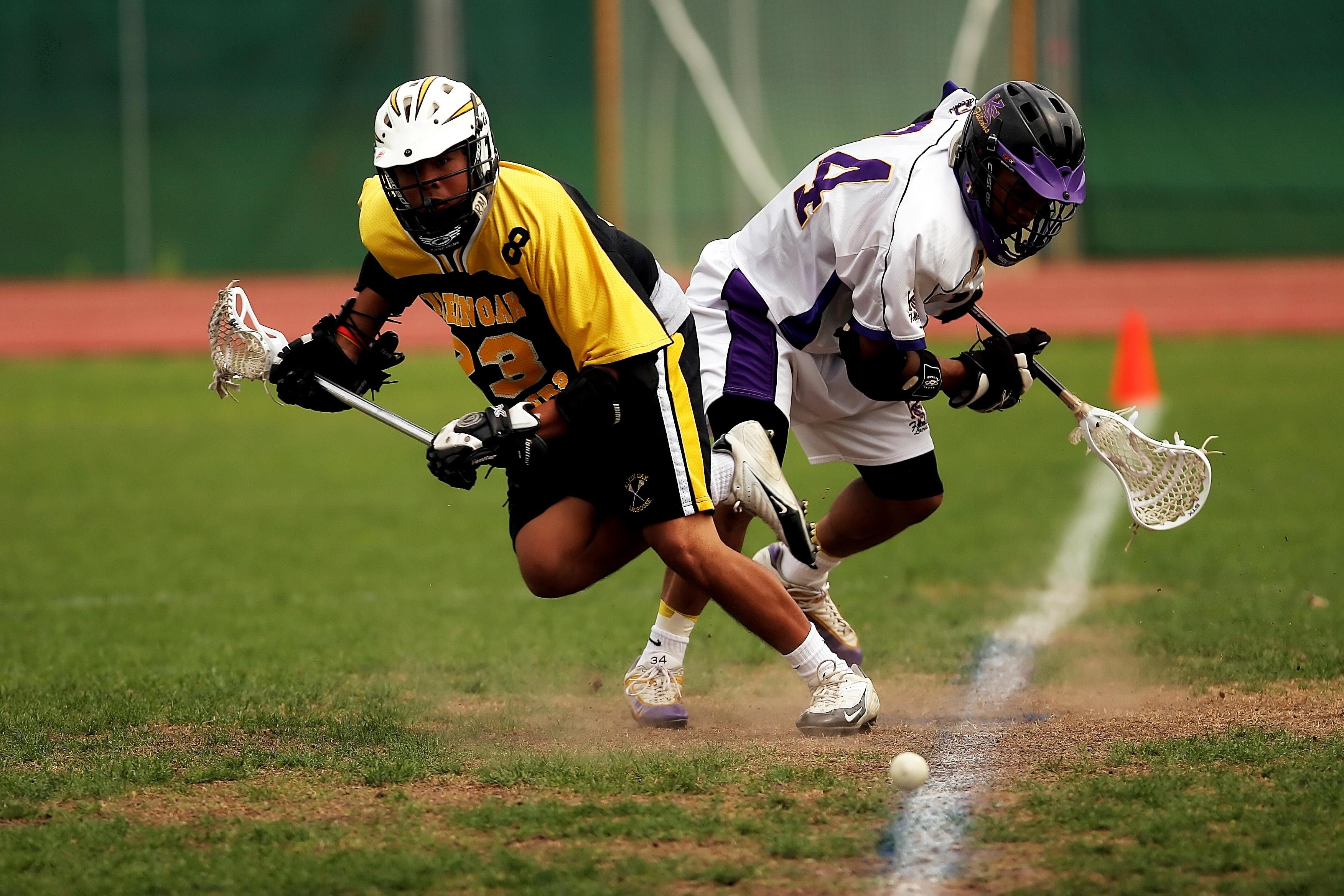Man wearing yellow and black sport jersey holding lacrosse stick photo