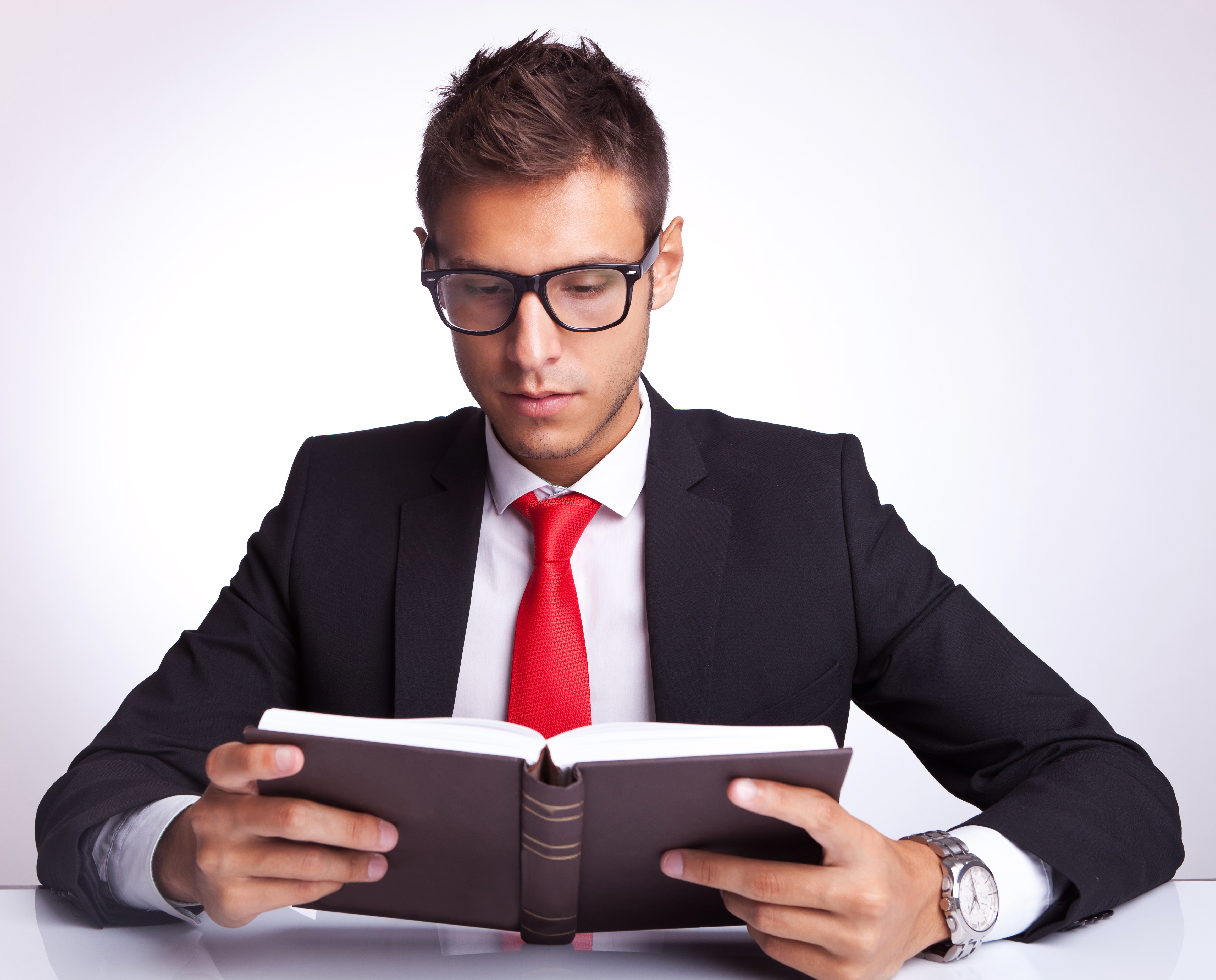 business man wearing glasses reading a book - Mpasho News