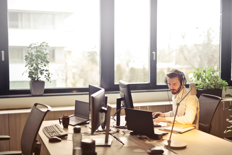 Man with headphones facing computer monitor photo