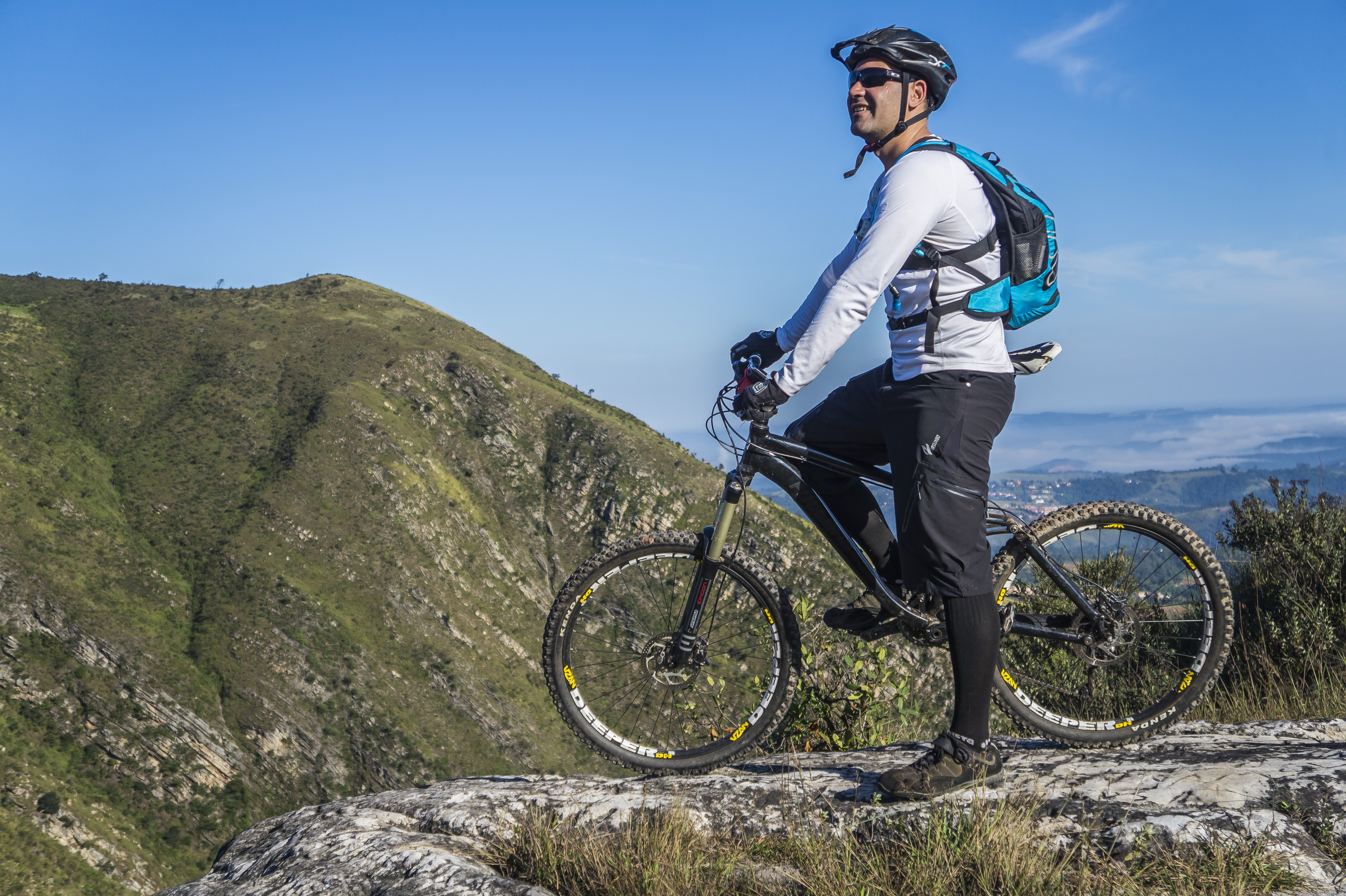 Man with white shirt riding abicycle on a mountain photo