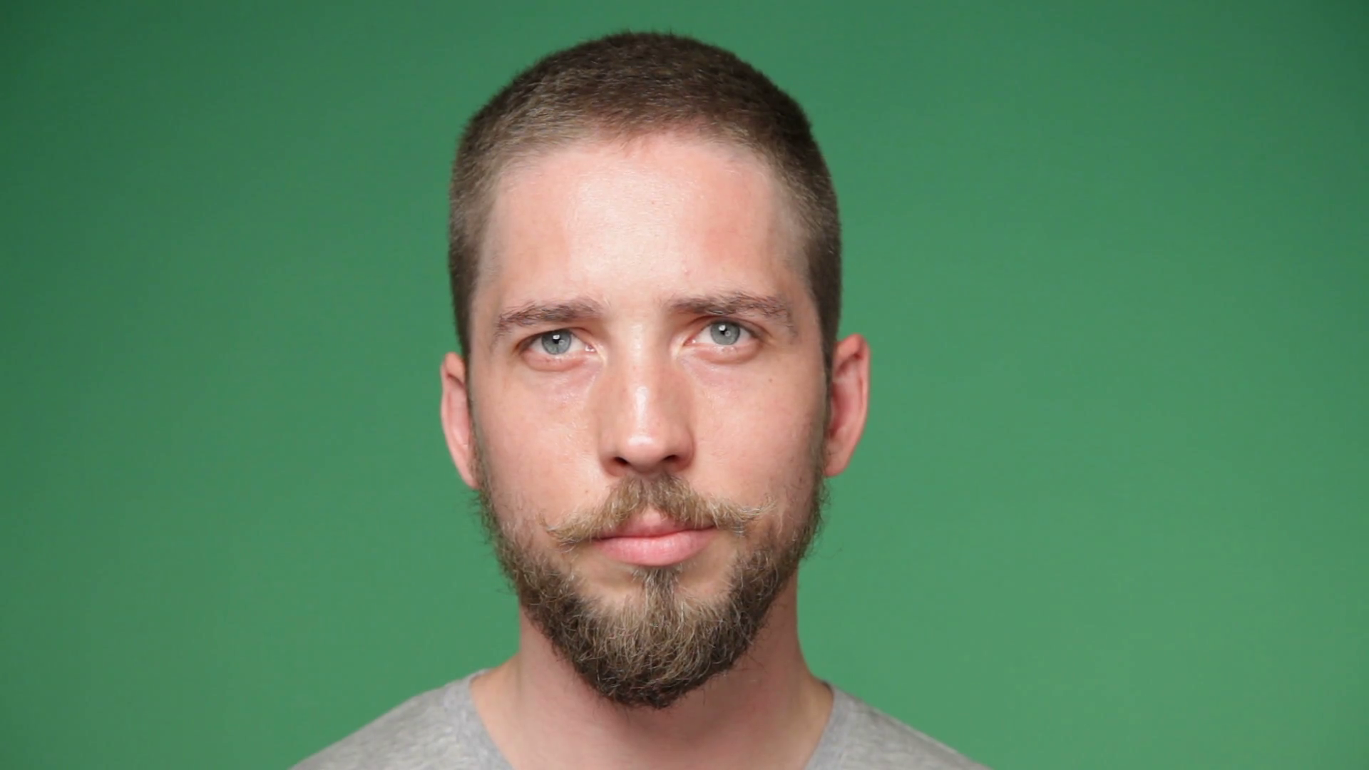 Close up serious man's face with trendy beard and mustache, green ...