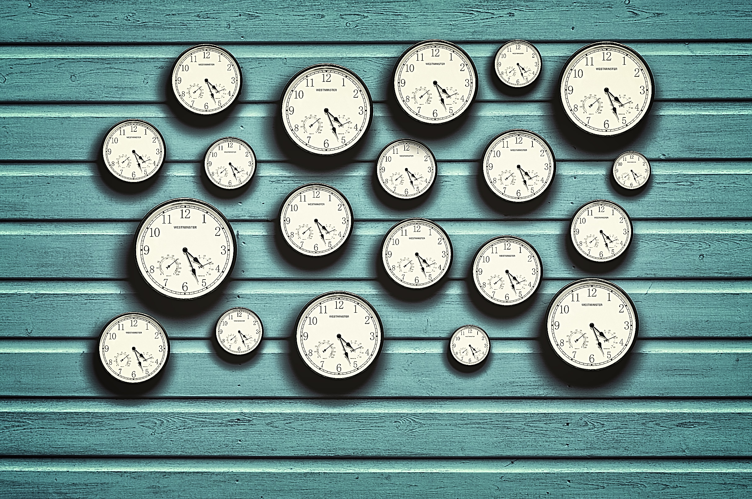 Many clocks in a blue wooden background photo