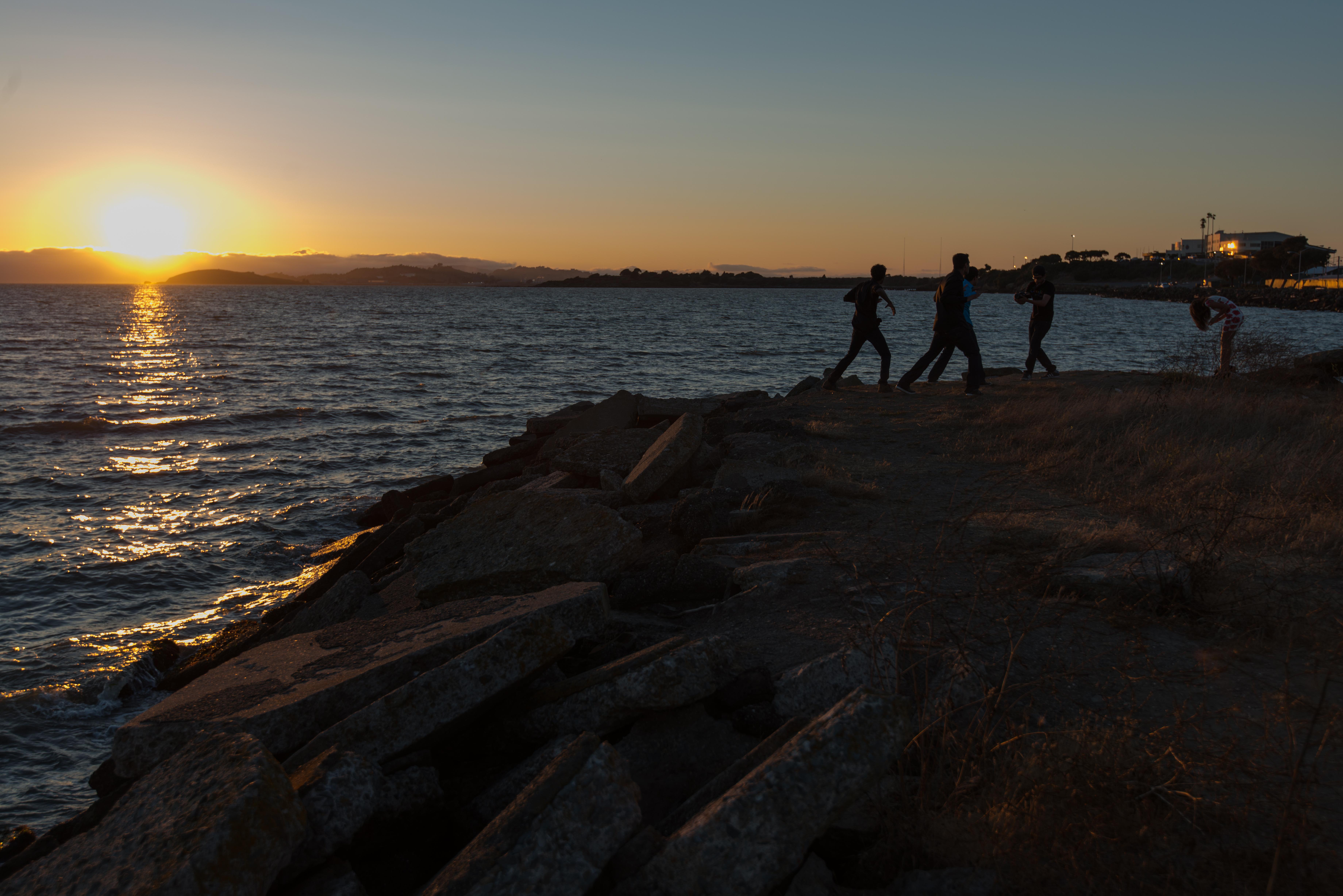 Men dancing on rocky outcrop in front of setting sun, Coast, Dusk, Landscape, Ocean, HQ Photo