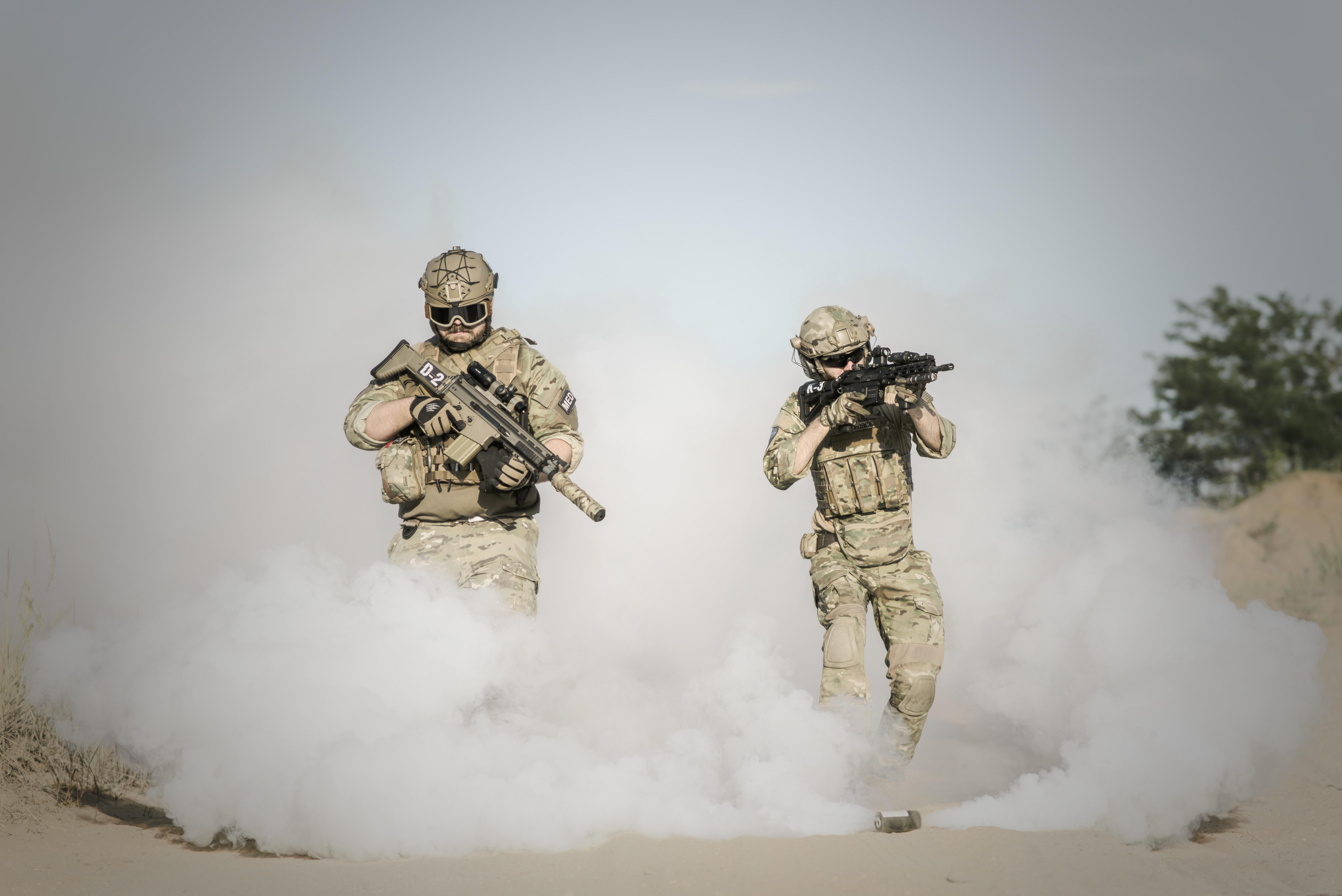 Men holding rifle while walking through smoke grenade photo