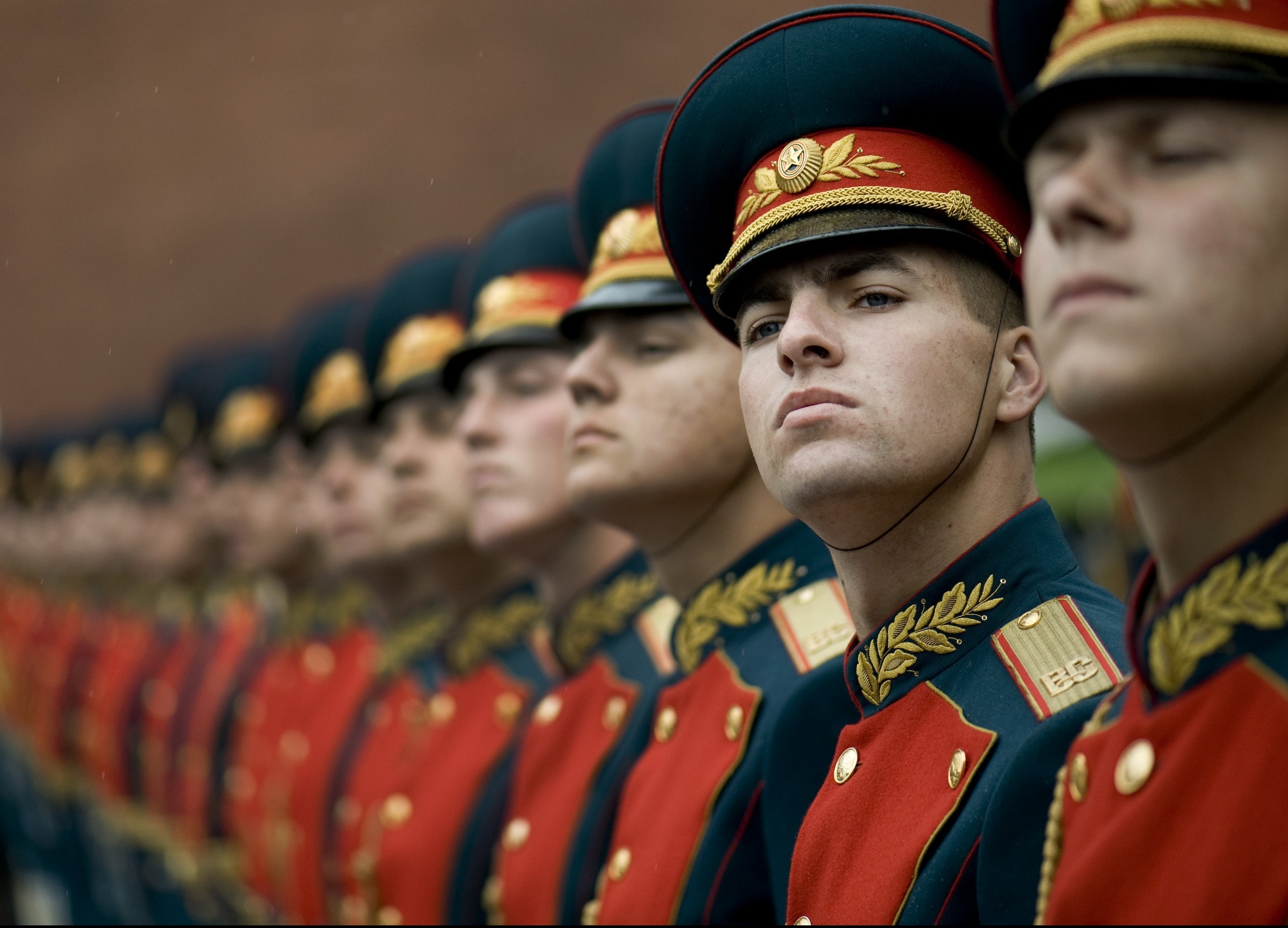 Men in black and red cade hats and military uniform photo