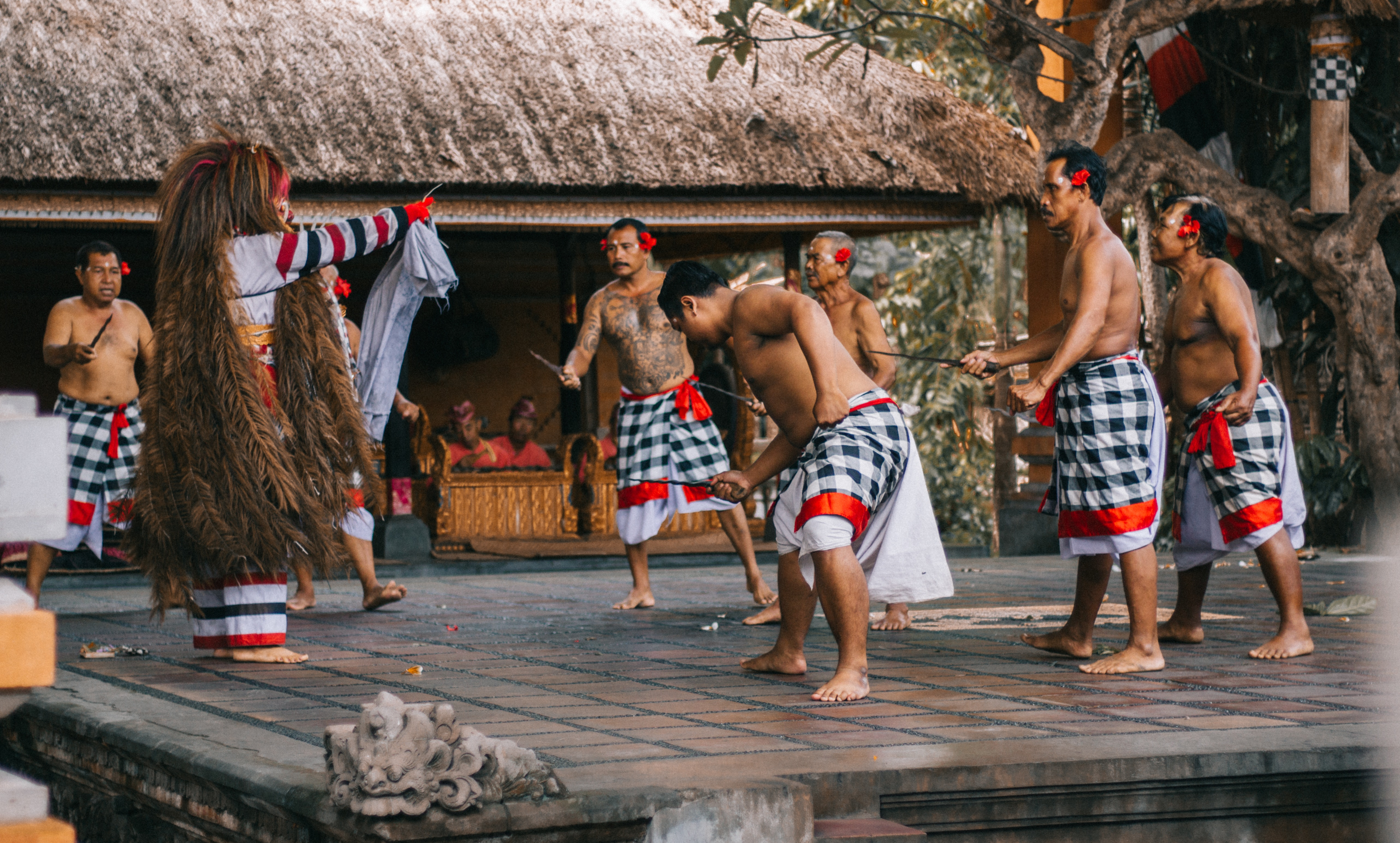 Men wearing white and black checked sarong standing on stage photo