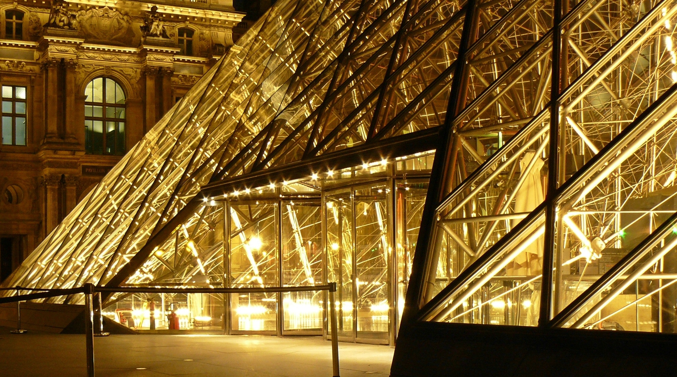 Metal frame glass pyramid outside a museum with yellow lights during nighttime photo