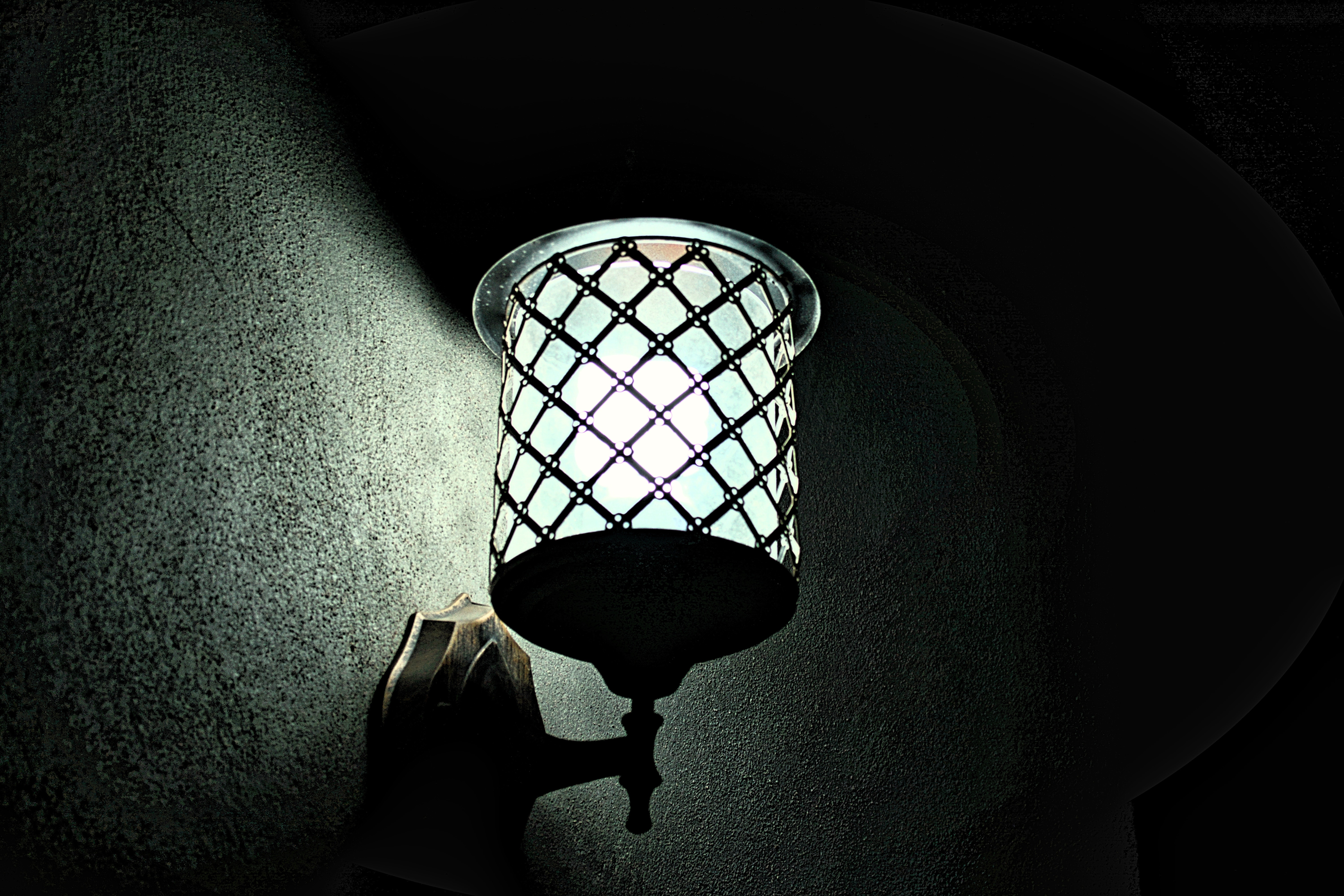 Metal sconce light switched on during night time photo