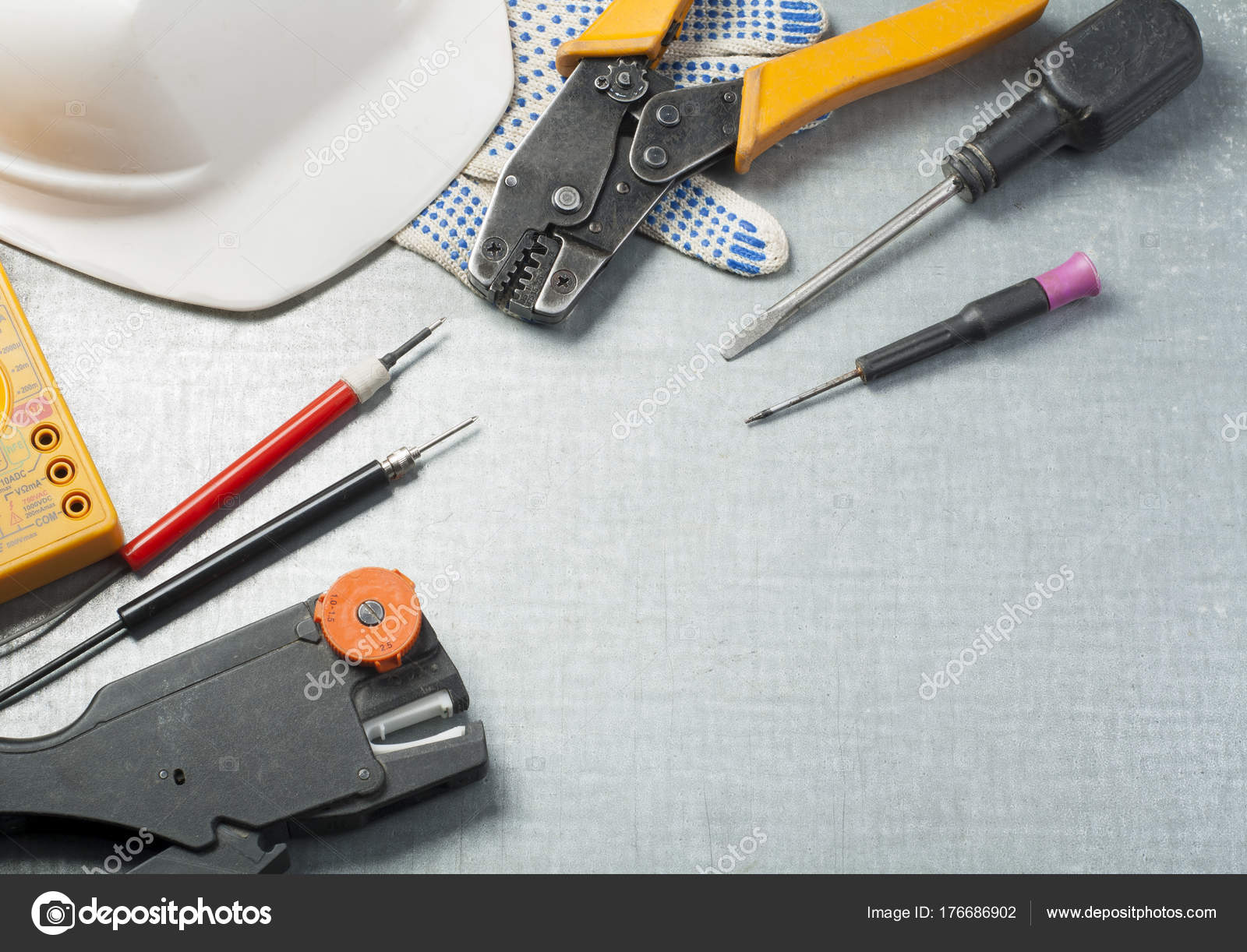 Set of electrical tools and white helmet on metallic background ...