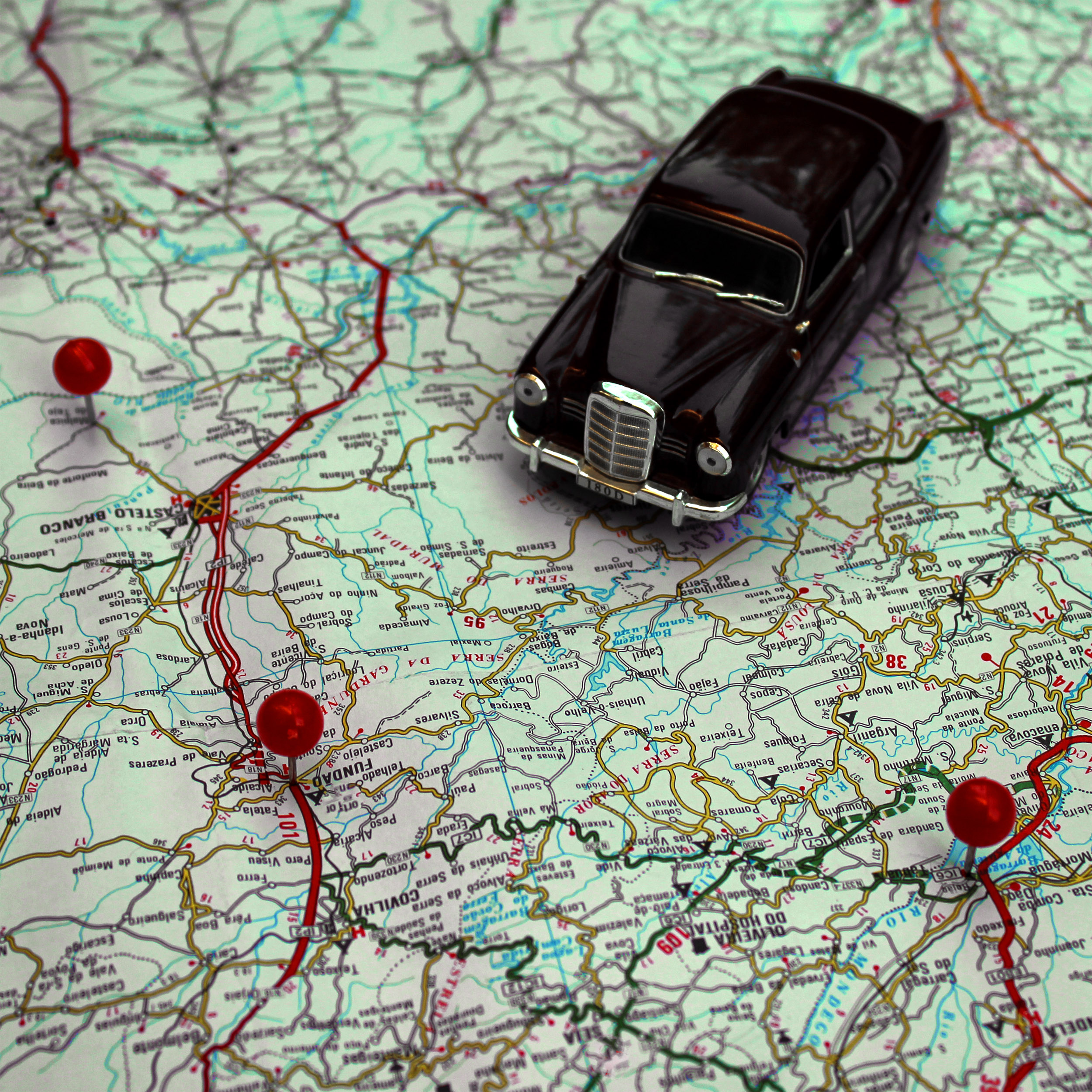 Miniature car and pushpins on a map - travel concept photo