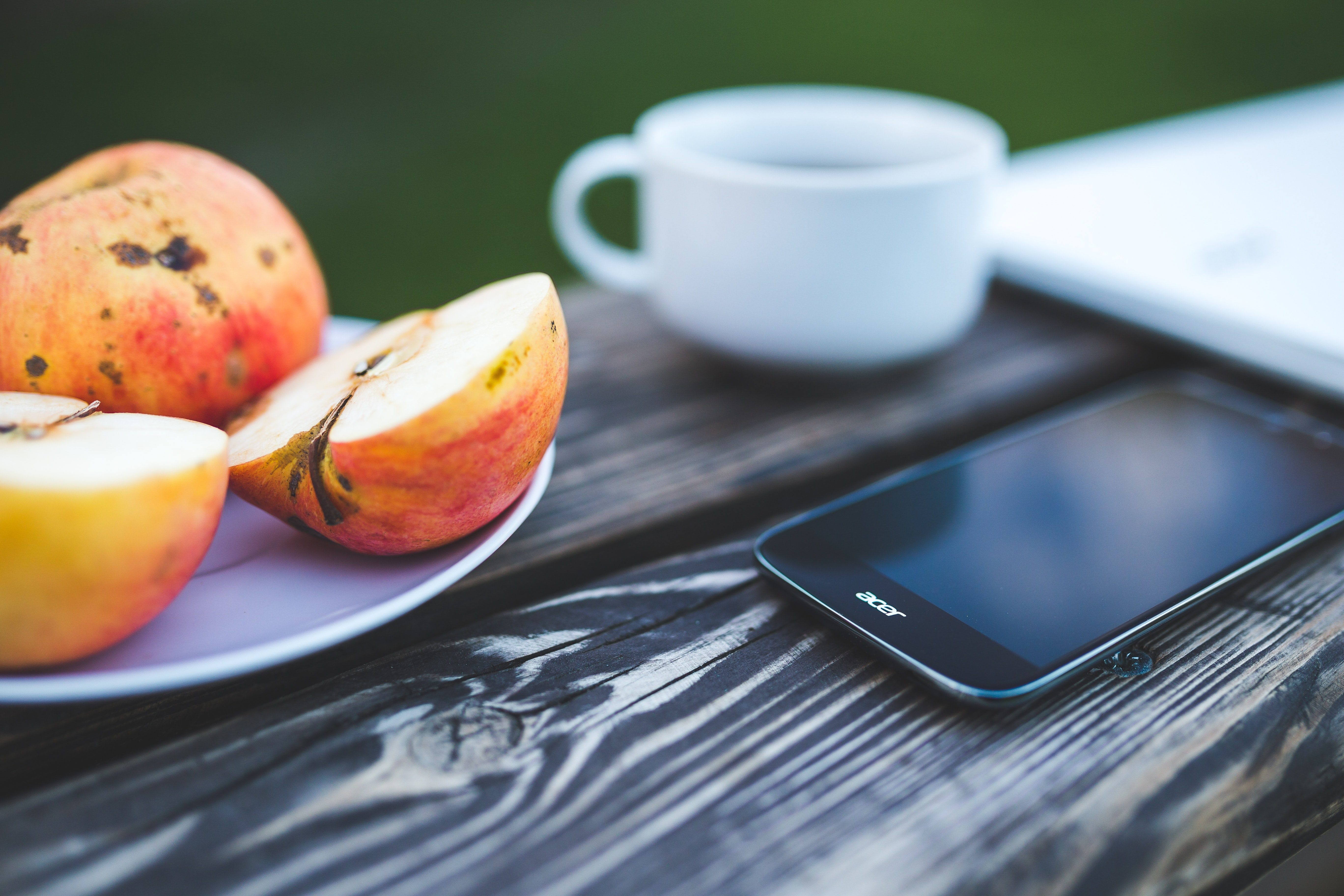 Mobile phone, apple, coffee on the wooden table photo