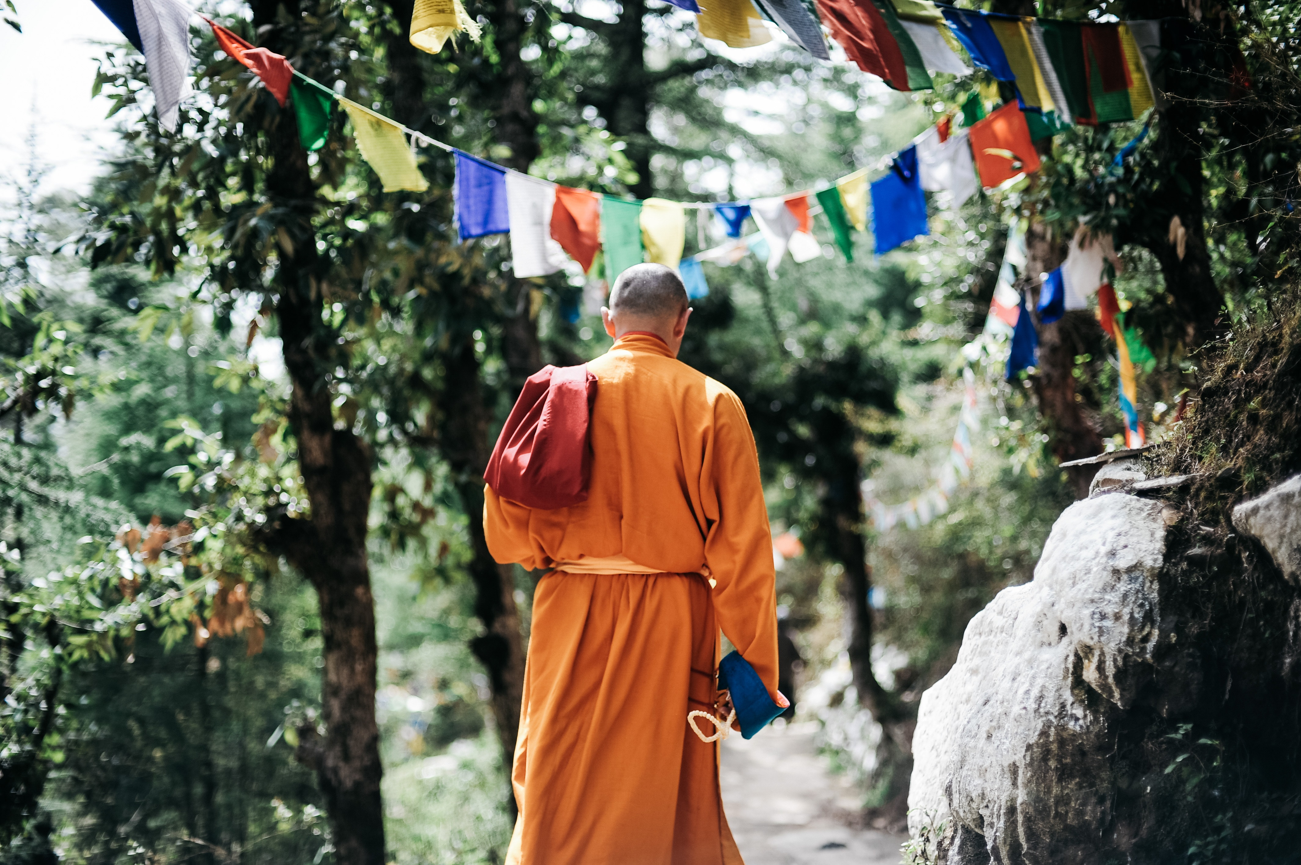 Monk walking near buntings during day photo
