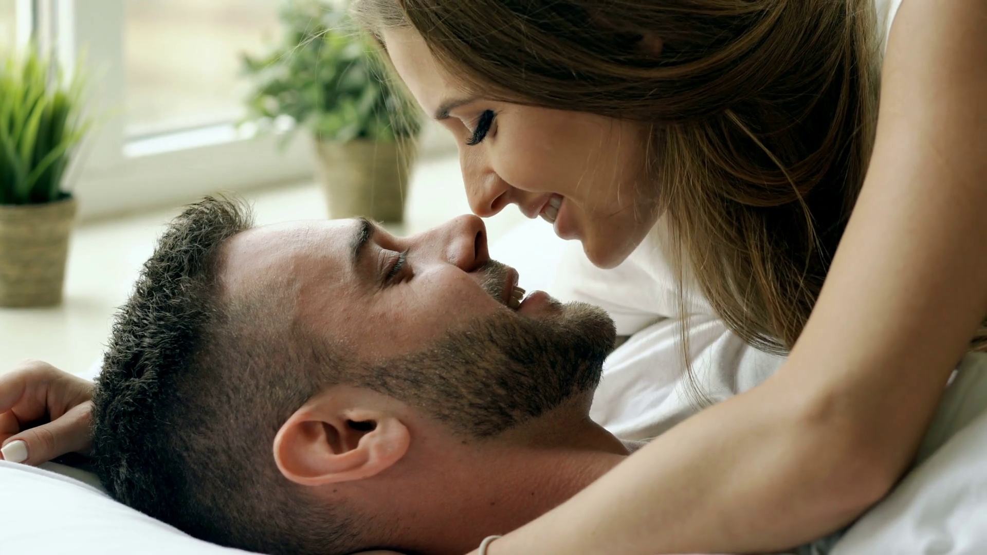 Young beautiful and loving couple kiss and hug into bed while waking ...