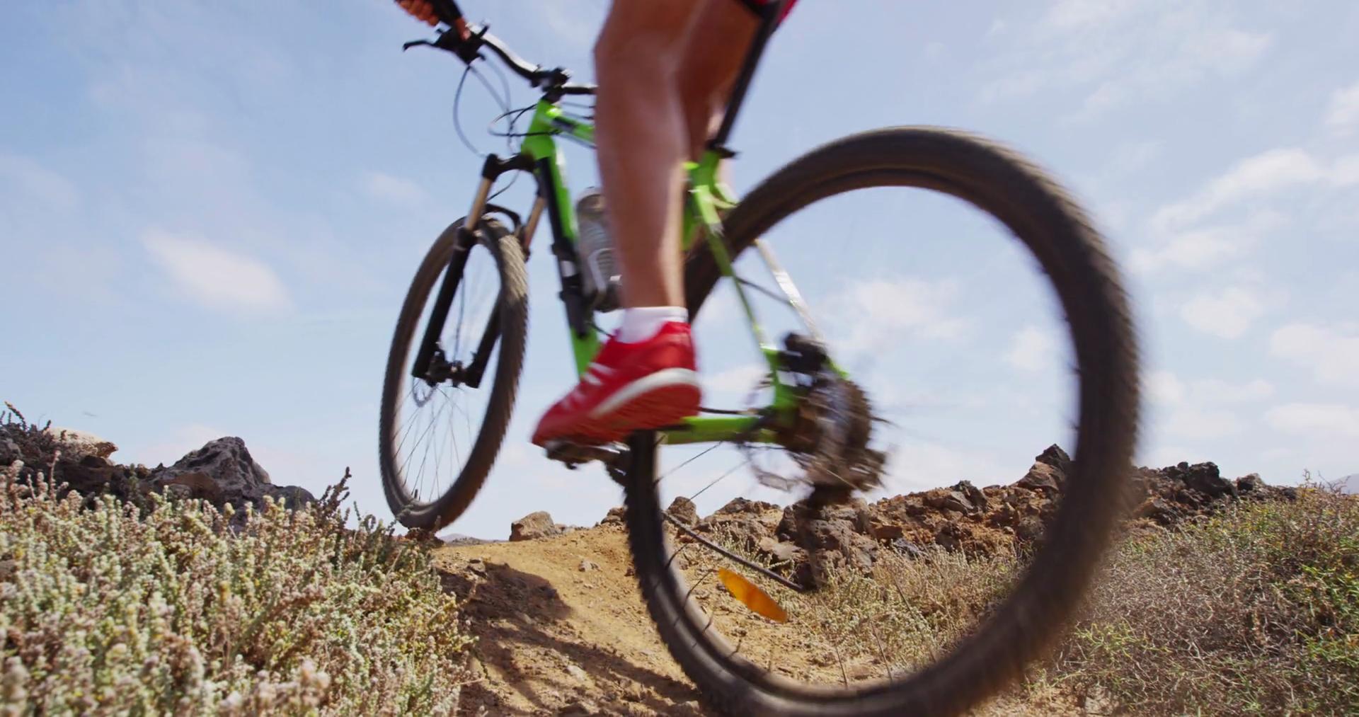 Mountain biker biking in slow motion on MTB mountain biking trail ...