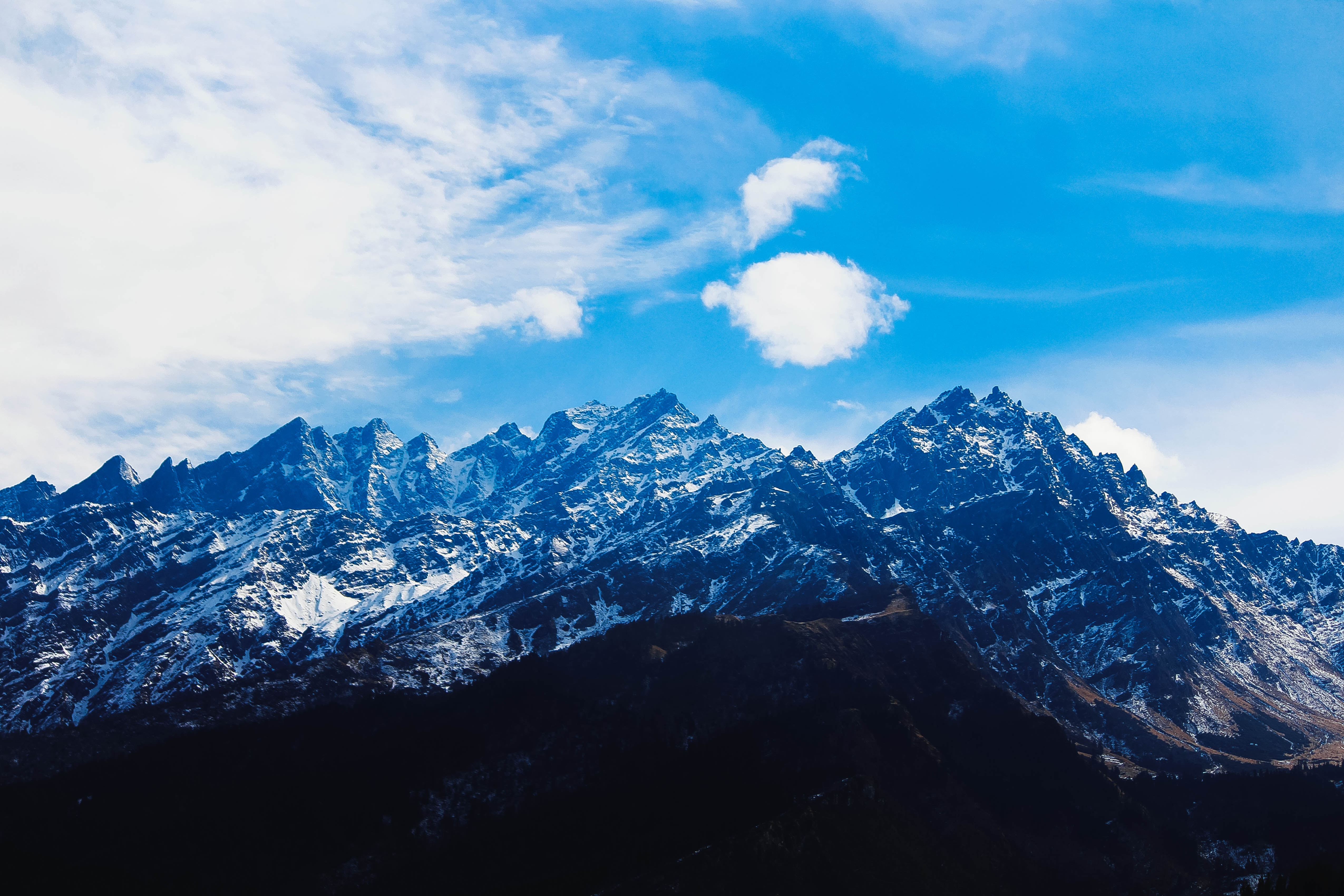 Mountain under white clouds at daytime photo