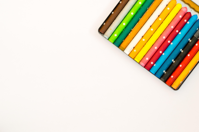 Multi colored pencils over white background photo