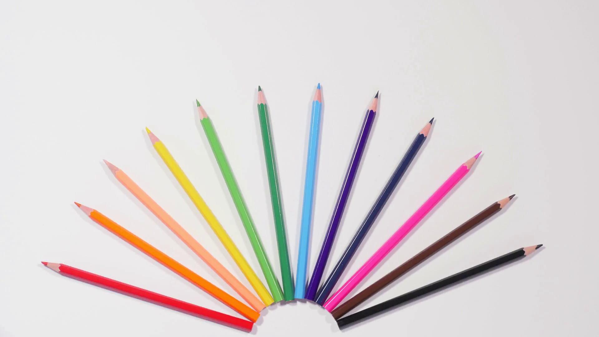 Multi colored pencils in circle swing around on white background ...