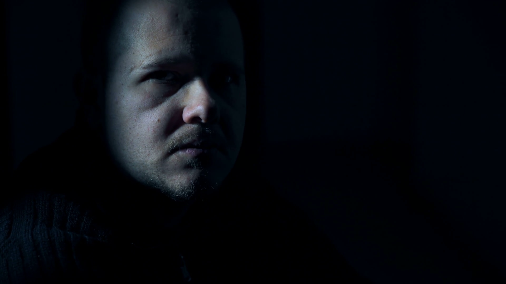 A mysterious man in the darkness, turns and looks at the camera with ...