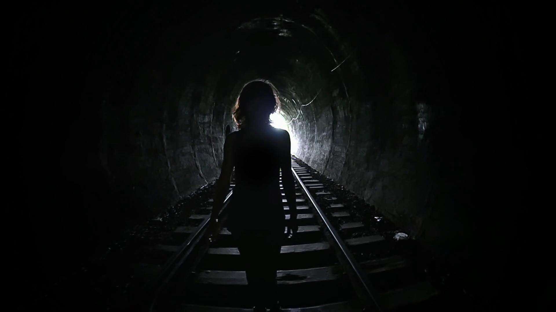 Mysterious woman walking in dark tunnel. Female silhouette on ...