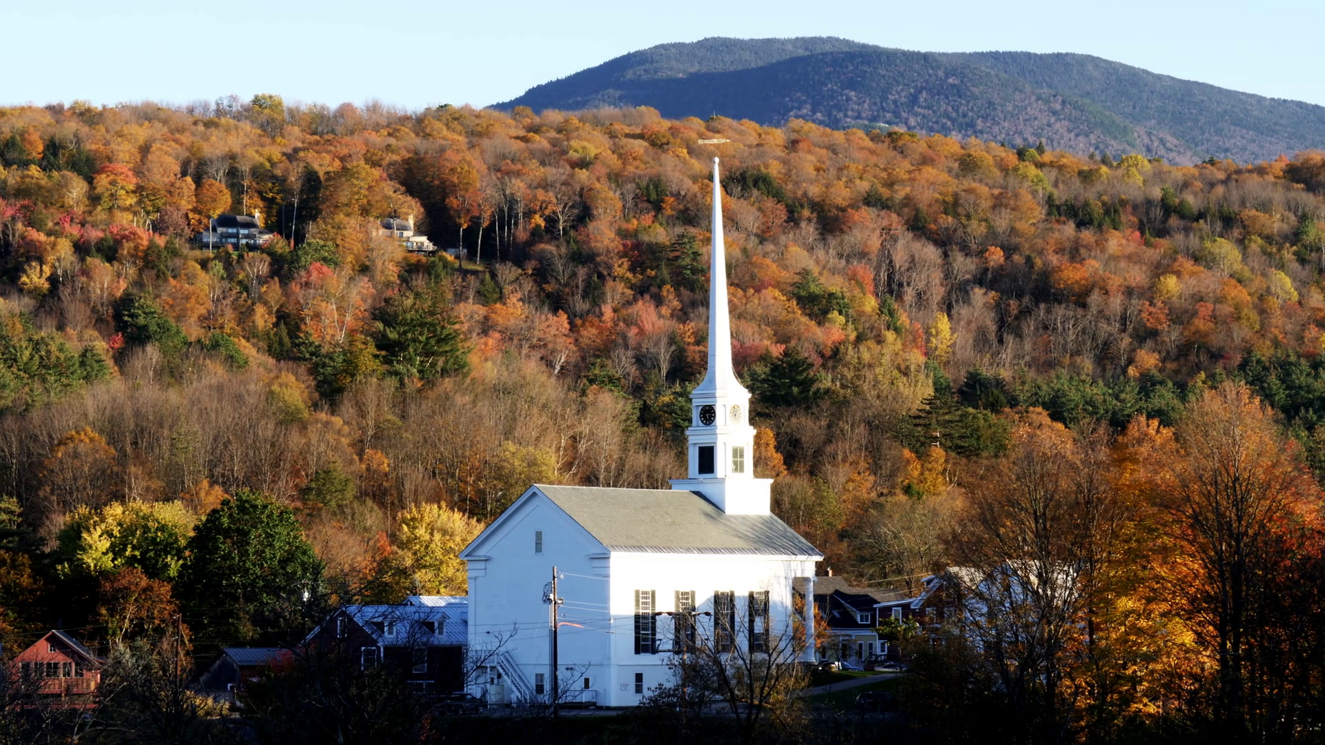 panning shot of a white new england church with a hillside covered ...