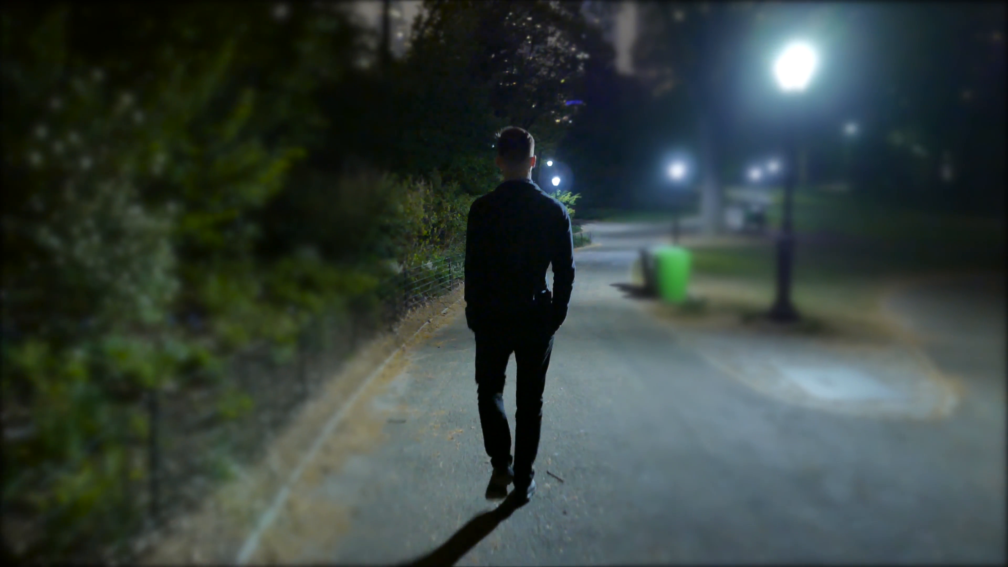 one man walking alone trough city park at night. spooky scary ...