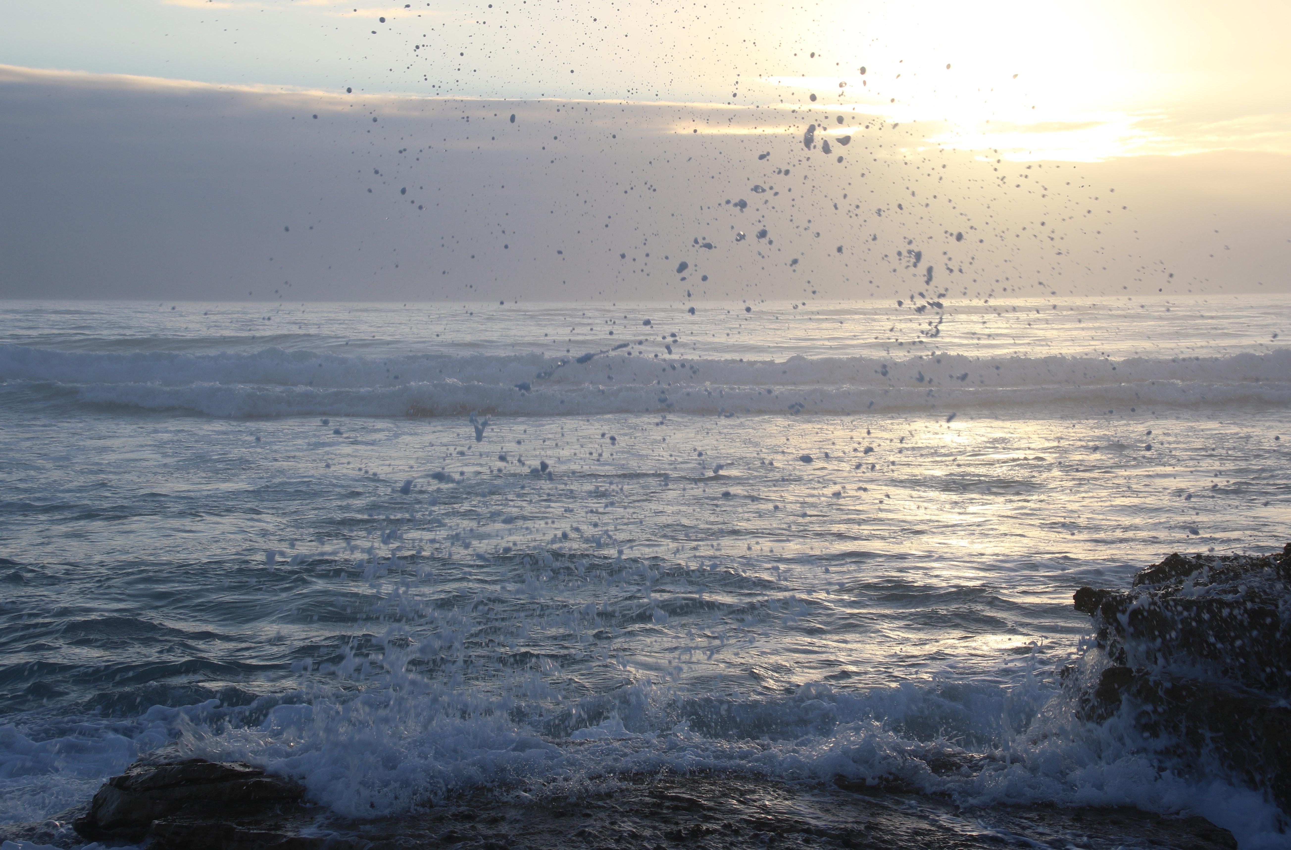 Ocean waves hammering rock boulder photo