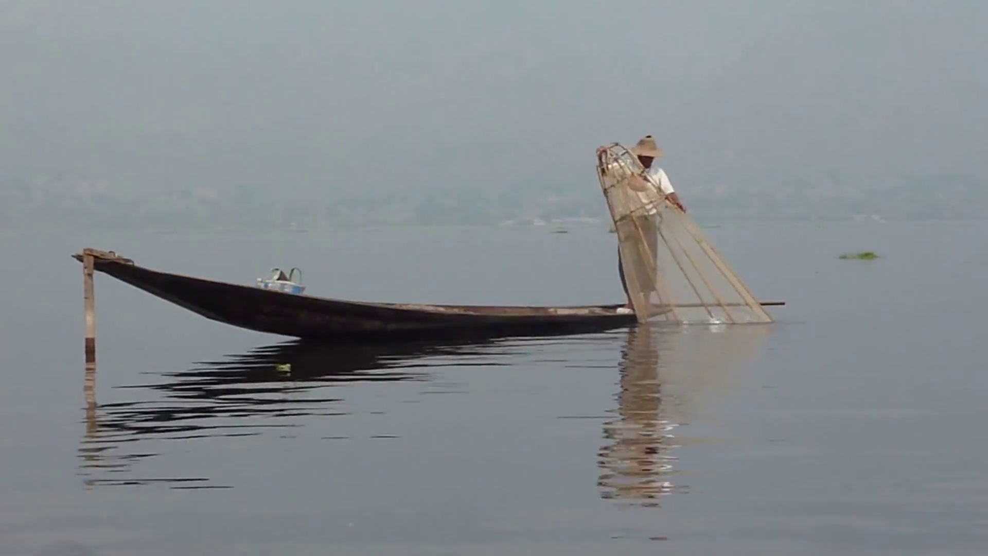 Traditional fisherman rowing on the old boat trough the pond Stock ...